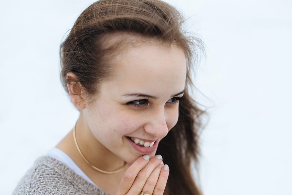 woman holding her chin while smiling