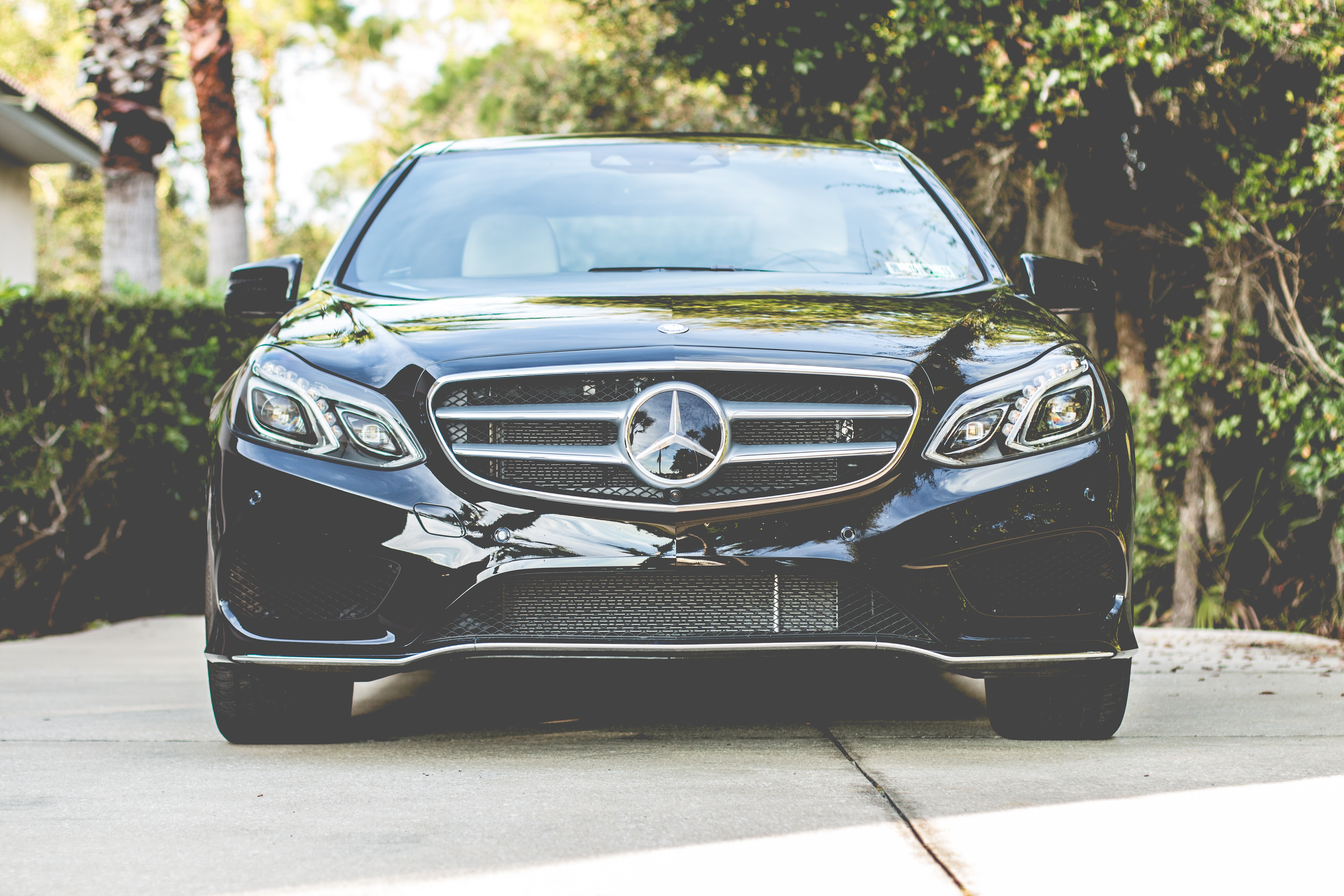 Front of the new luxury black Mercedes-Benz parked in a driveway.