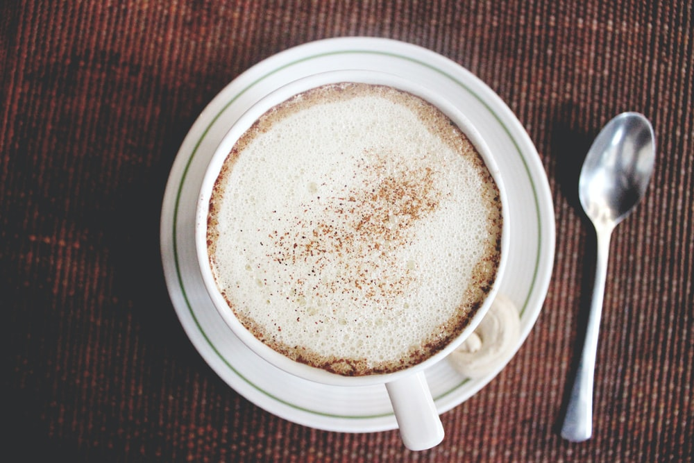 top view photo of white ceramic mug on saucer beside siver tablespoon
