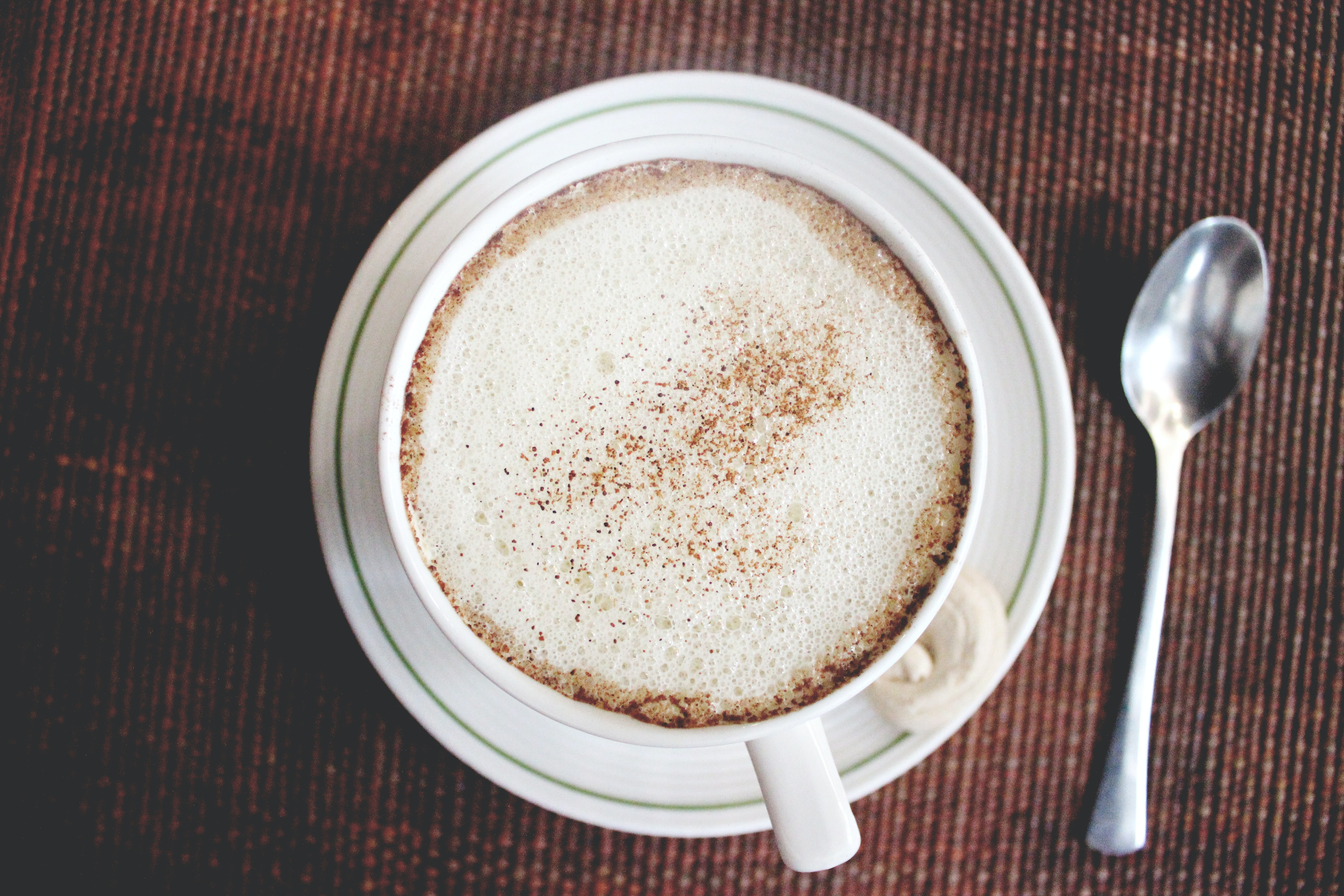 A frothy cup of coffee with cinnamon sprinkled on top of it in a white mug