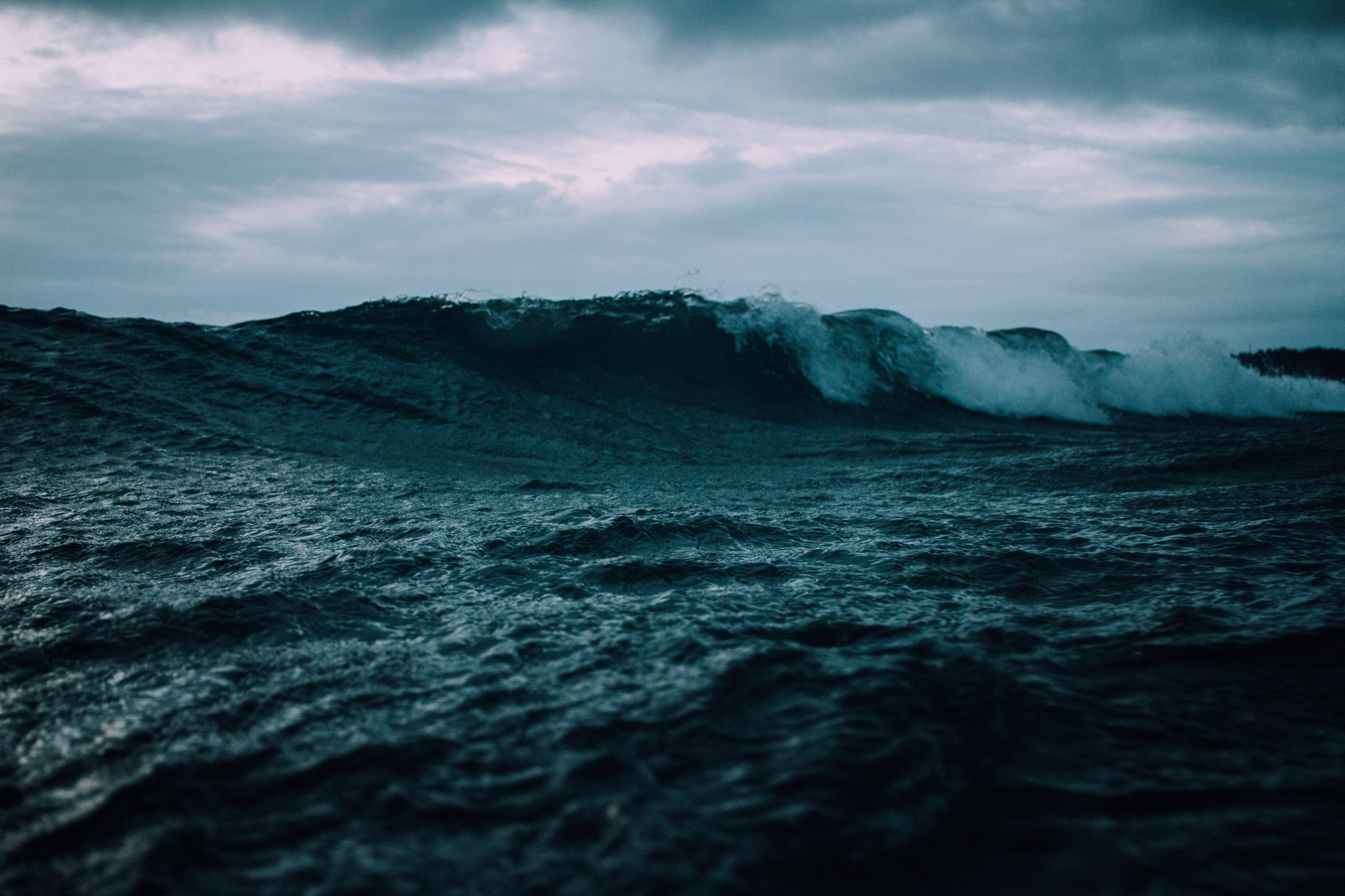 A wave rolling on a turbulent sea, beneath a moody cloudy sky at Omaha