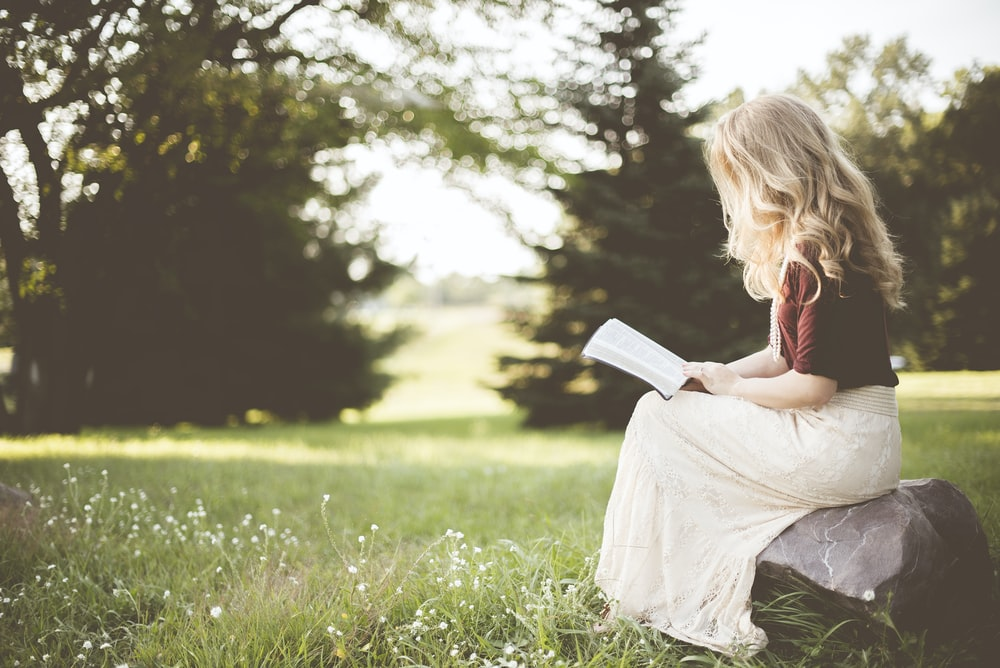 woman sitting while reading book