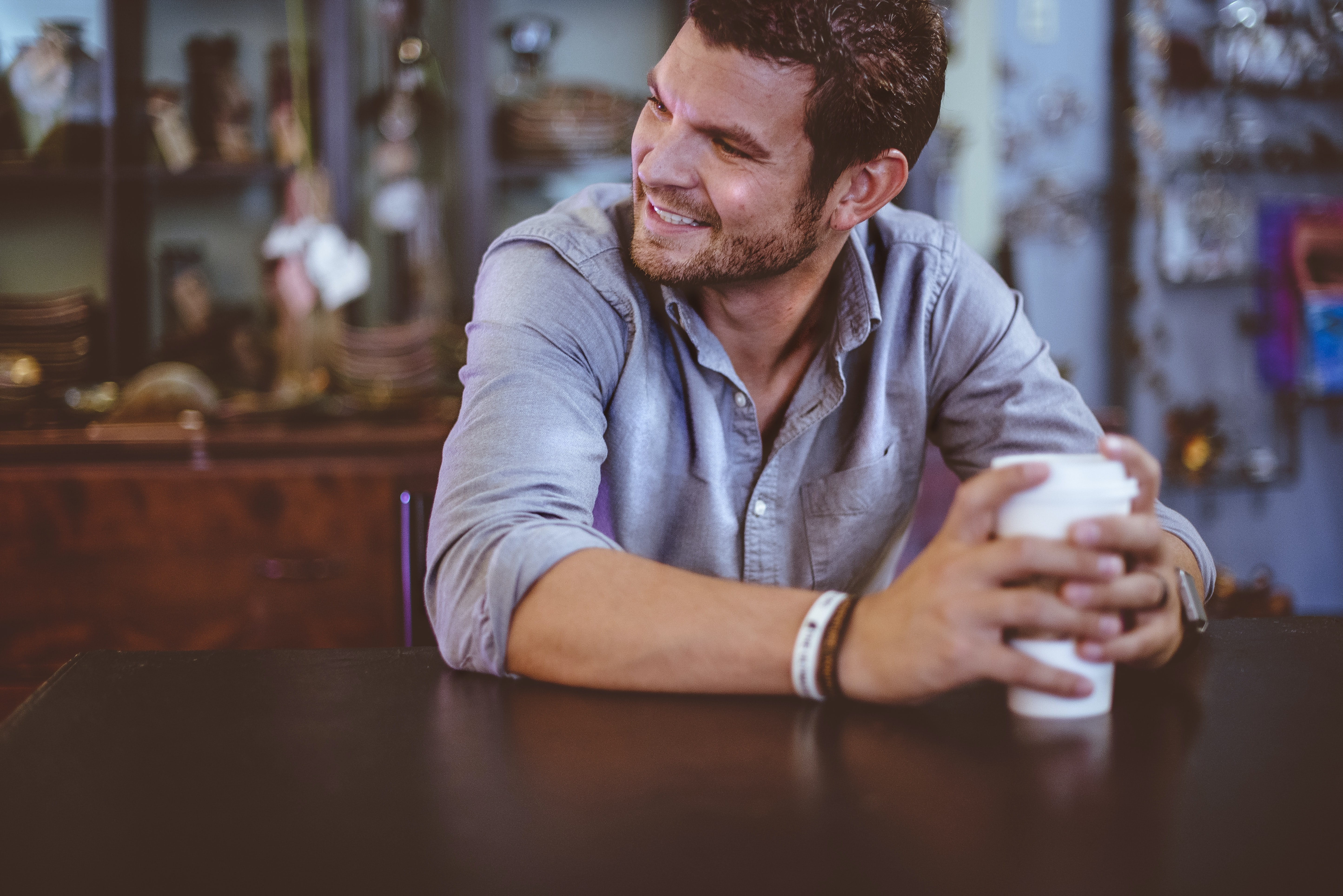 A man in a denim shirt sitting at a table and clutching a cup of coffee