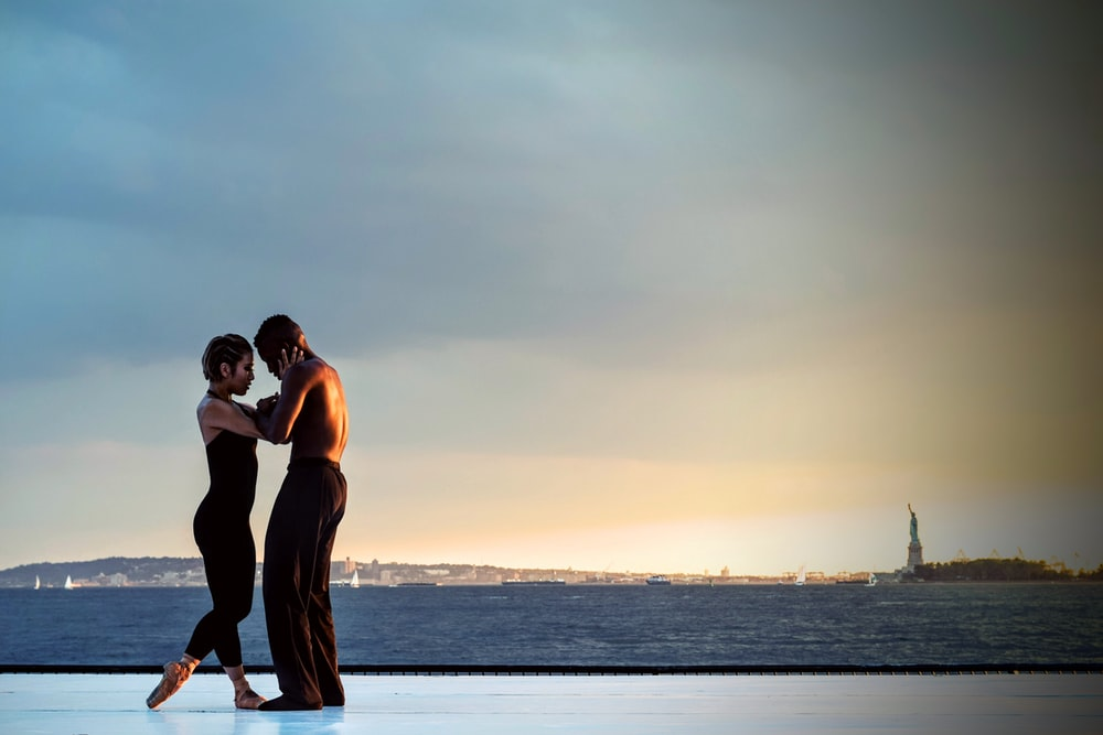 couple standing near body of water during daytime