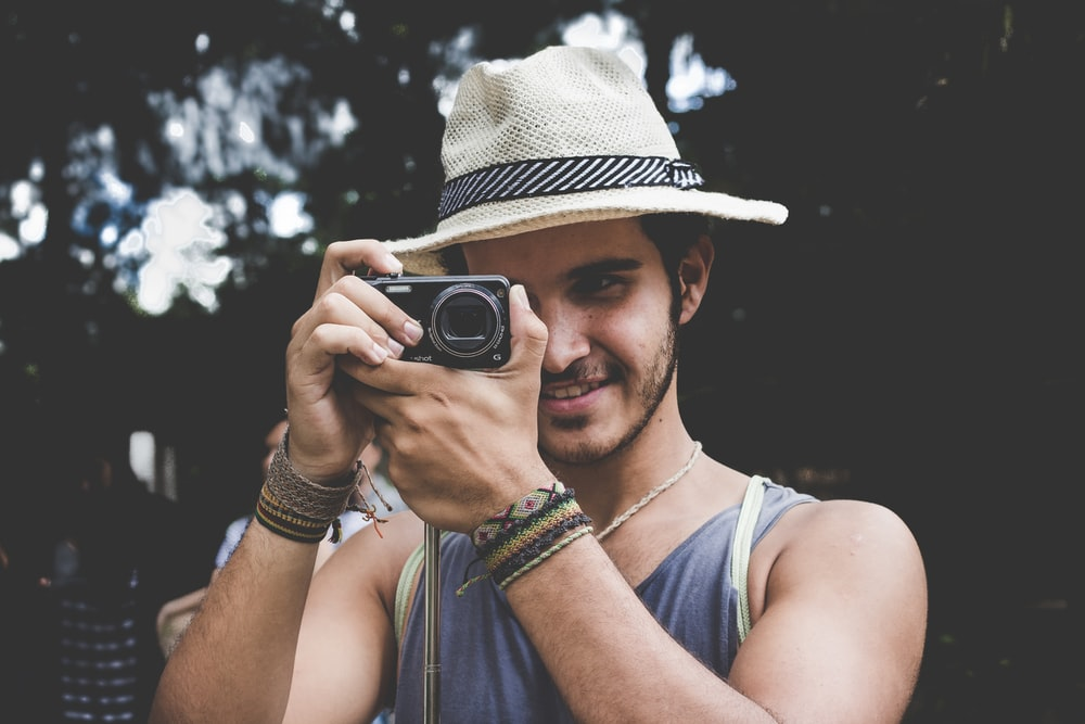 selective focus photo of man holding black compact camera