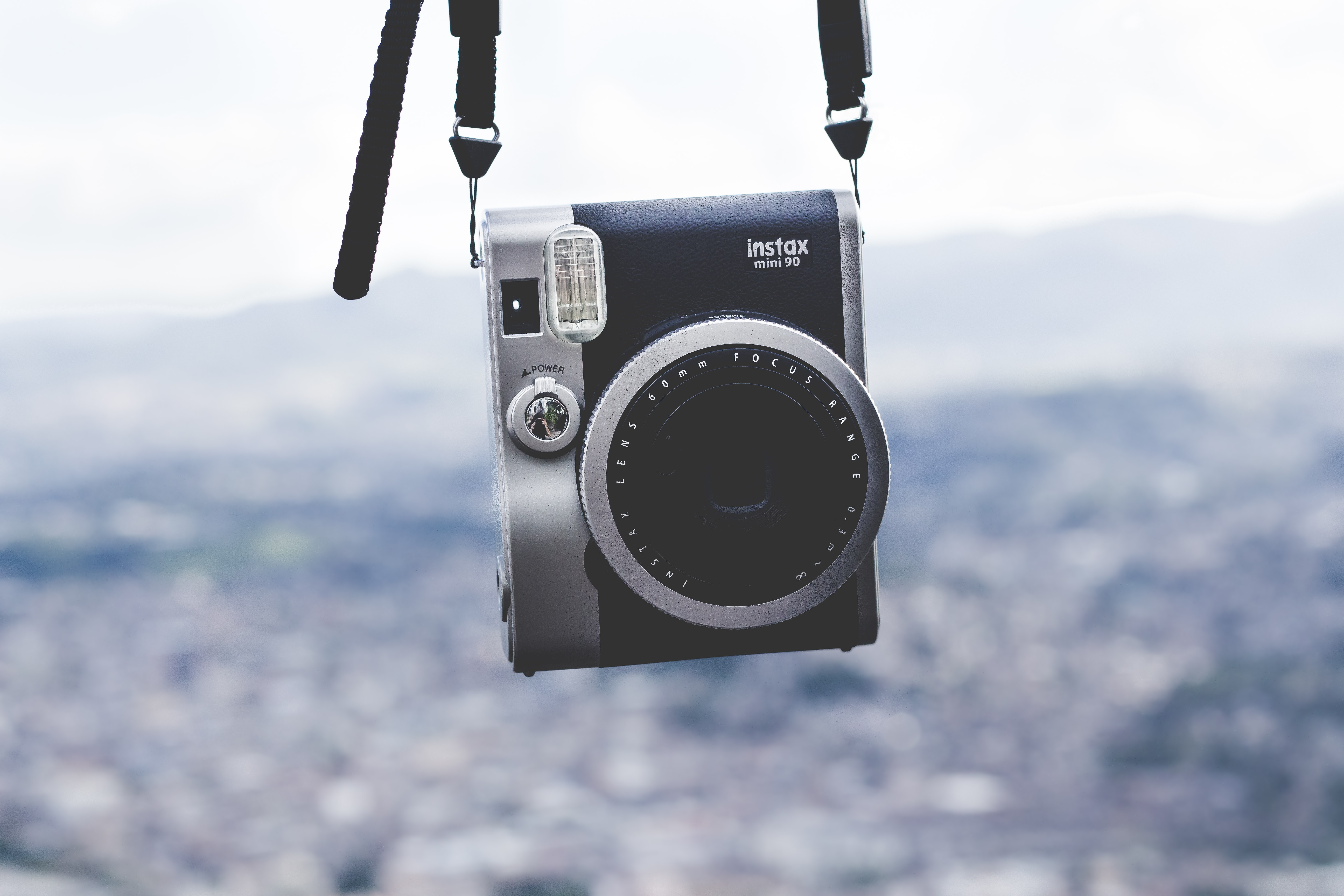 An Instax mini 90 camera dangling from above over a blurred background depicting a city or outdoor scene