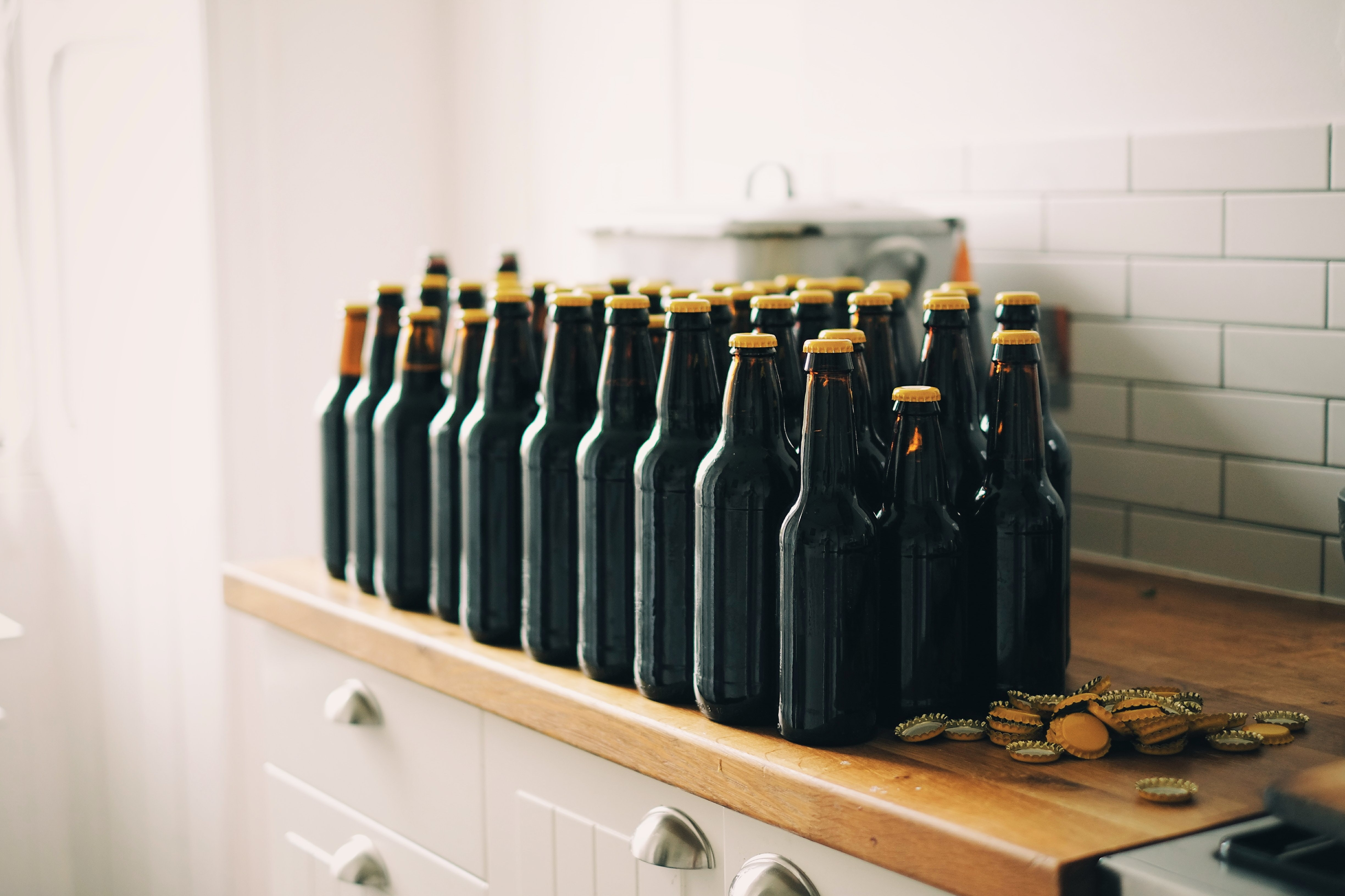 black tinted glass bottle lot on brown and white wooden cabinet