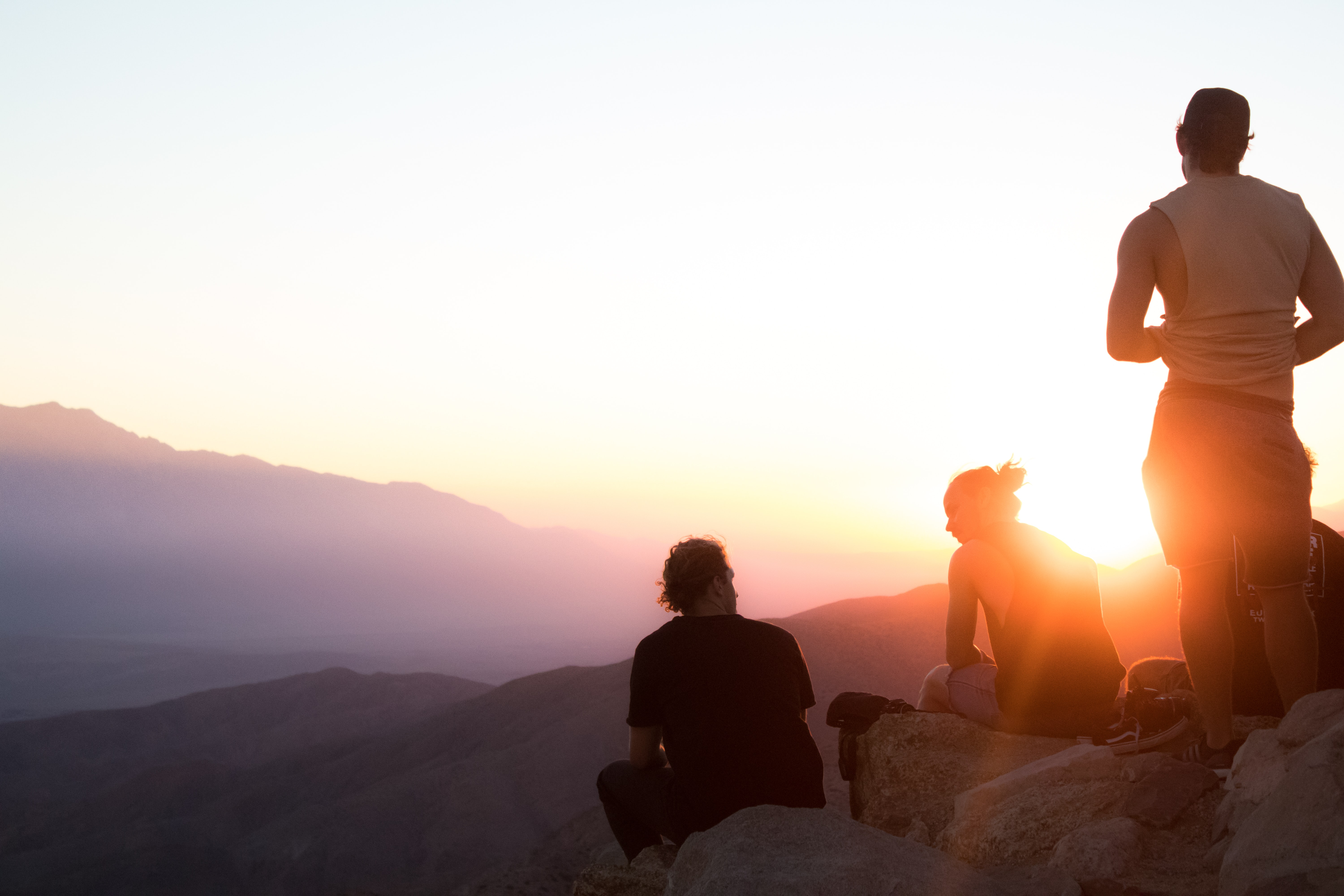 Group hikers atop a rocky cliff taking a break by watching the sunset at Joshua Tree