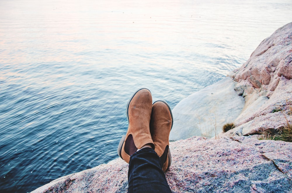 A person sitting on top of a rock resting their feet next to the ocean water.
