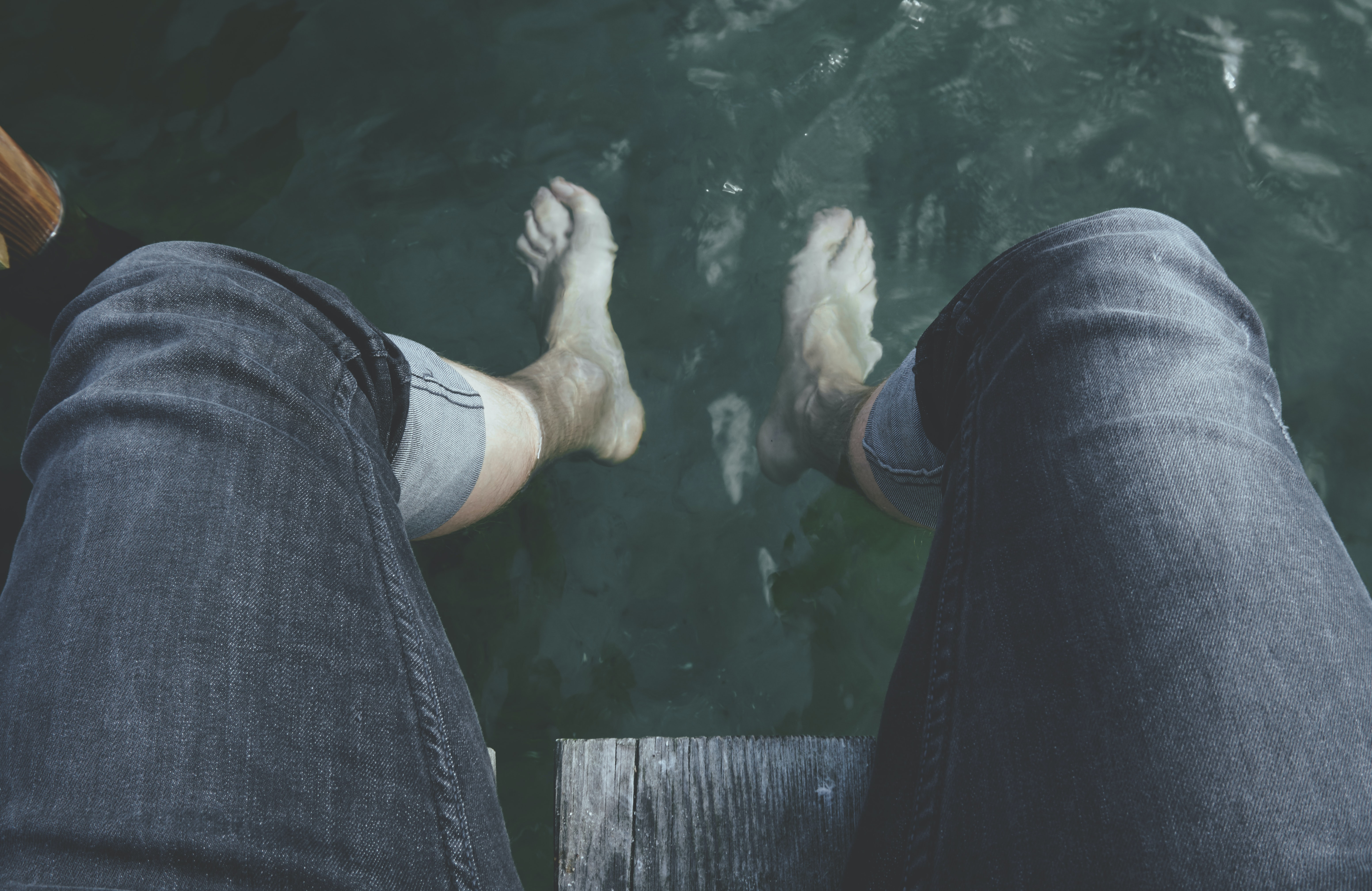 View from the thighs down of a man's feet dangling underwater in Faaborg.
