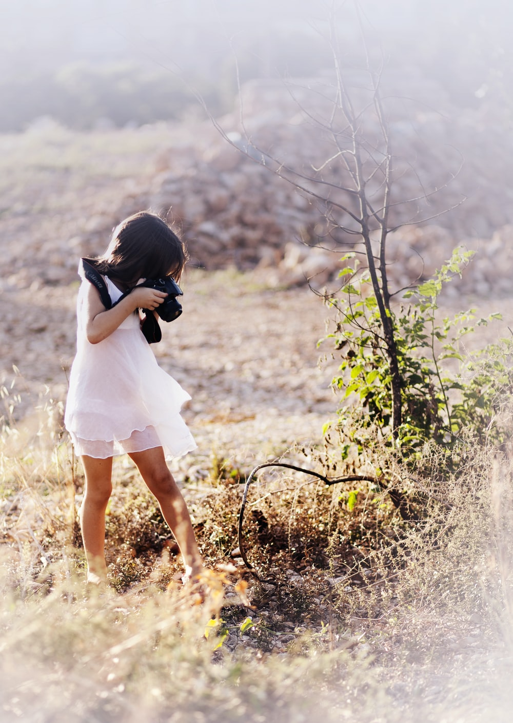 girl taking picture of tree branch outdoors