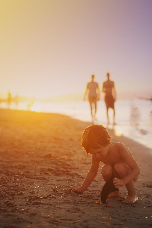boy playing sand on seashore during sunset