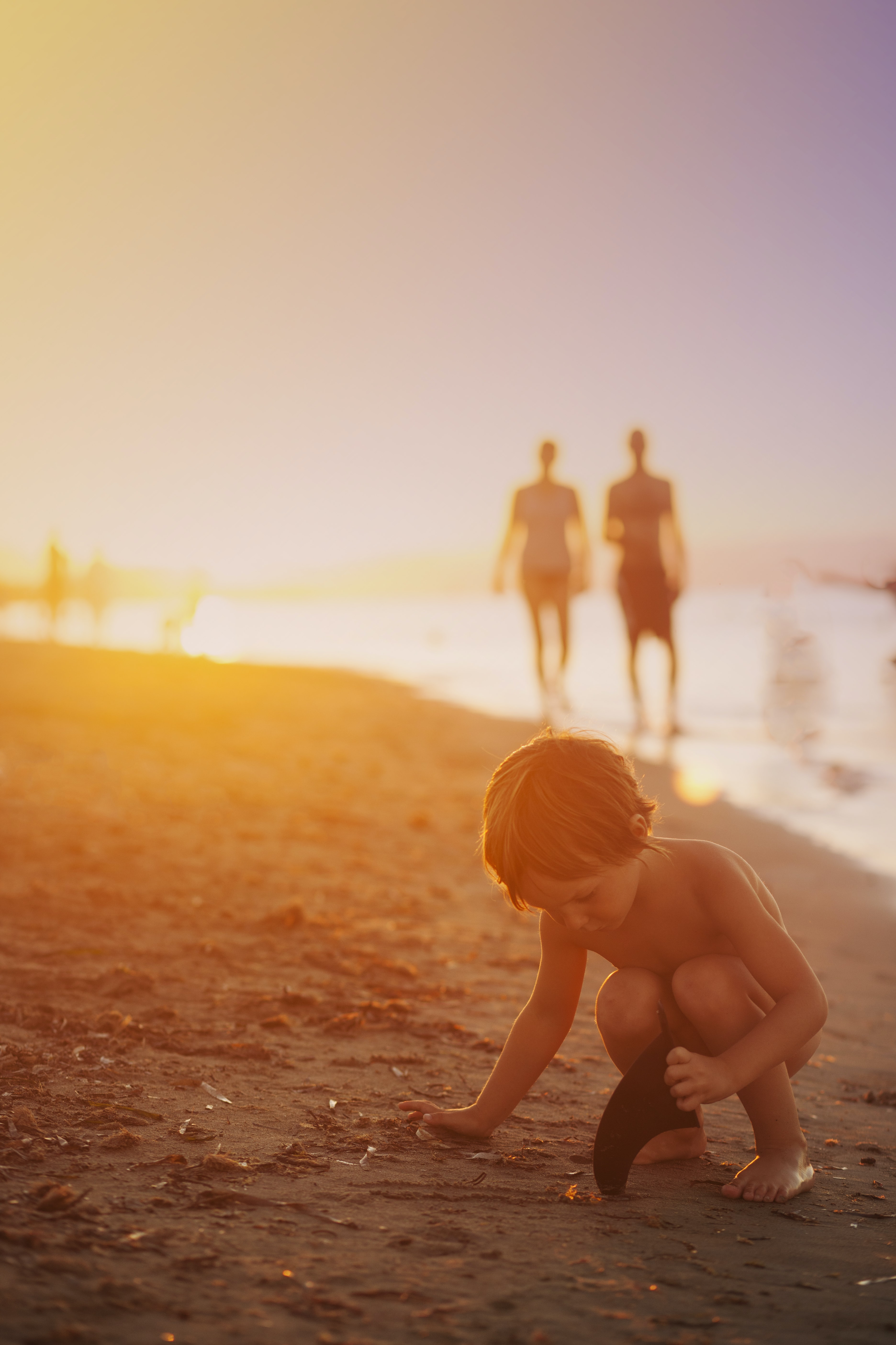 boy playing sand on seashore during sunset