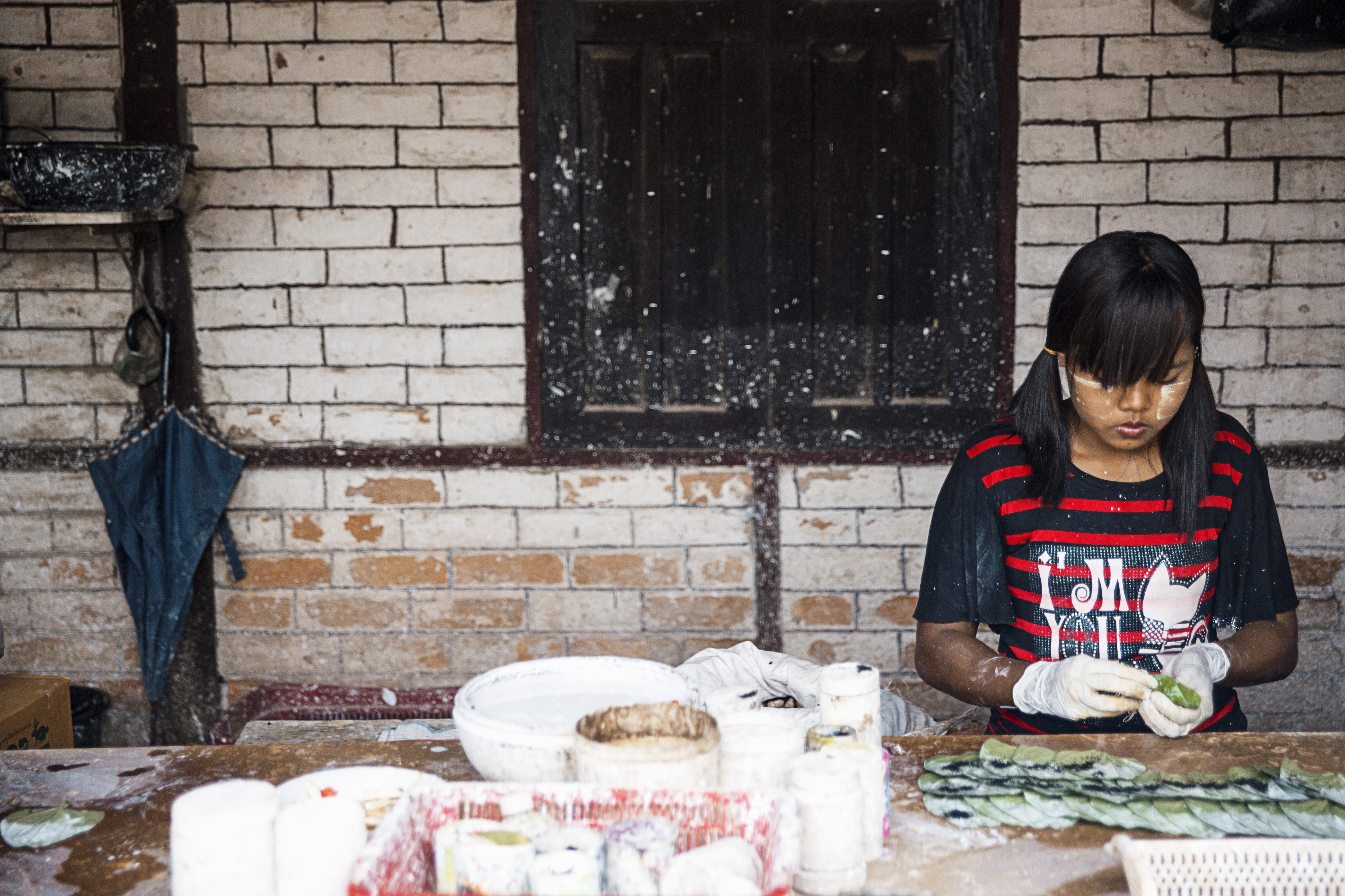 A dark skinned girl doing crafts outside.