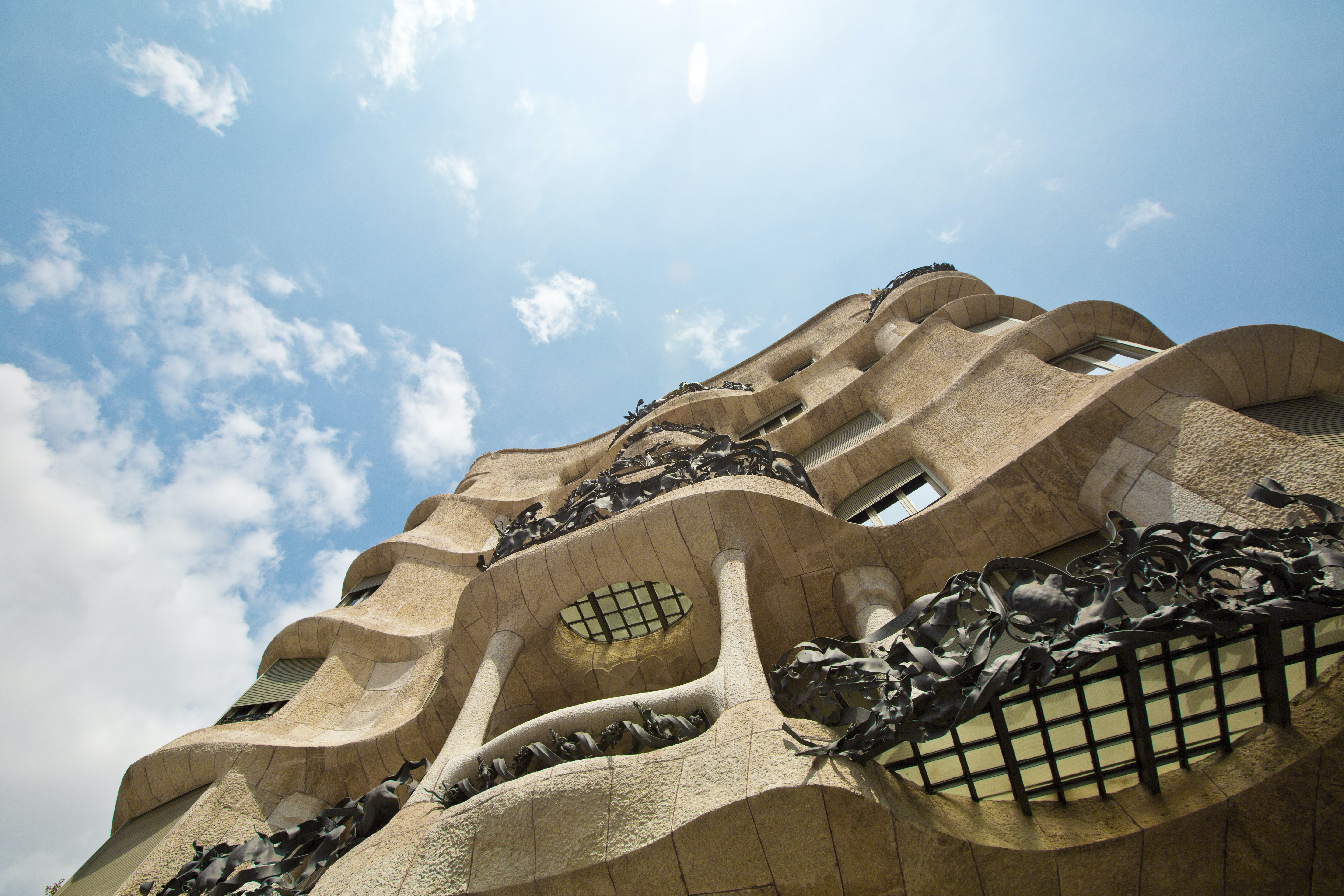 The facade of a building with sandstone architecture and blue sky with clouds in the background
