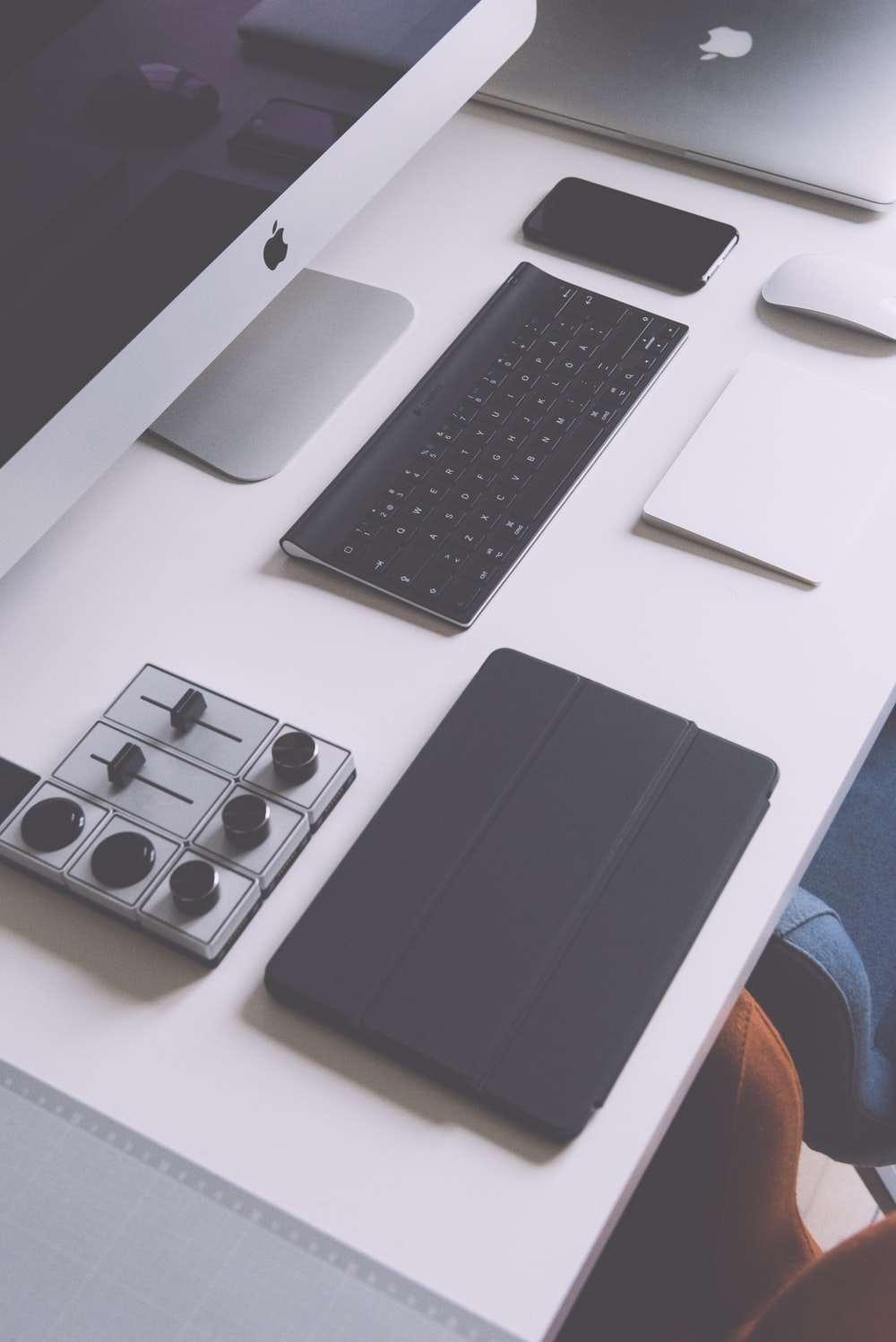 flat lay photography of black iPad case, Apple wireless keyboard, iMac on white table