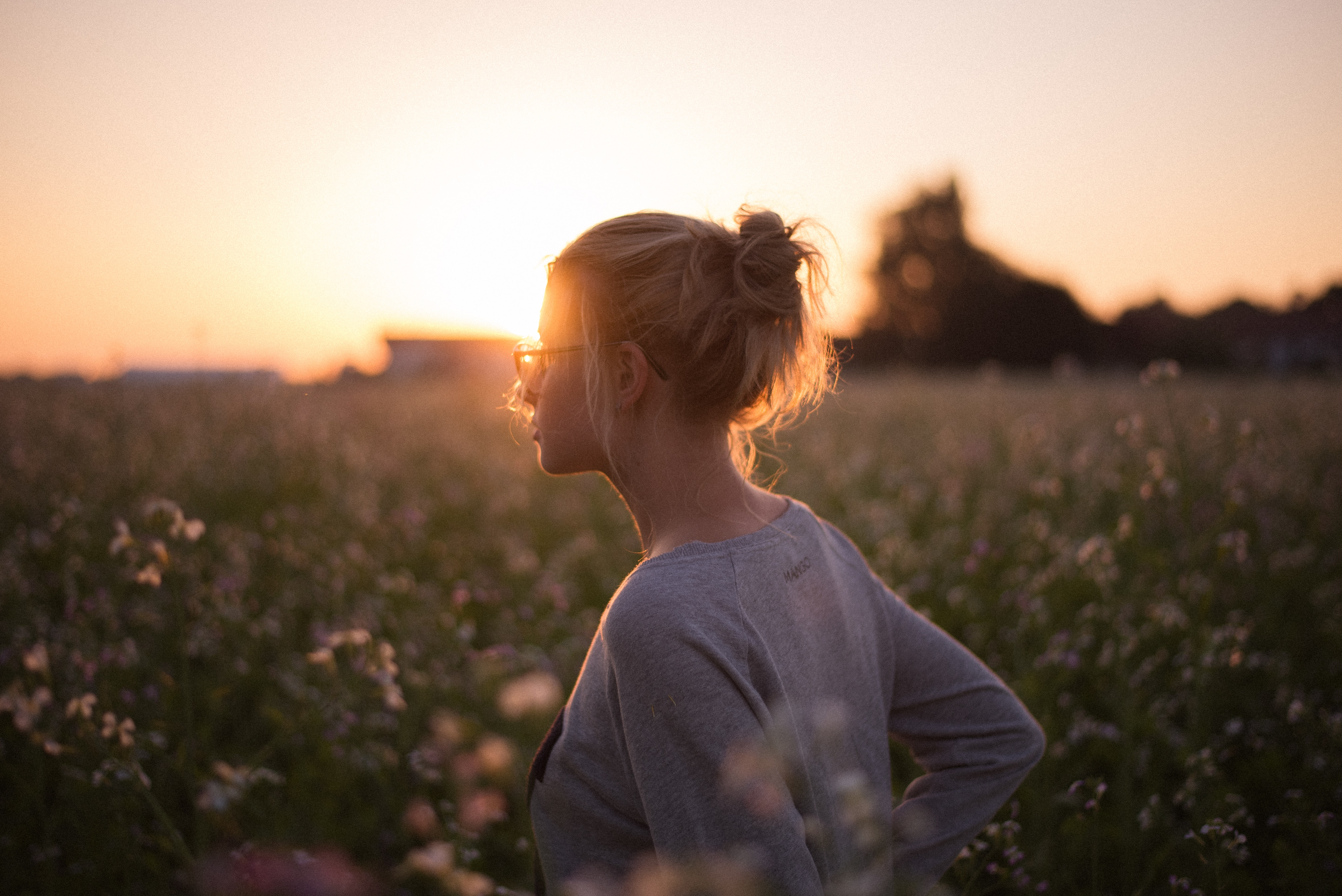Woman in a messy bun and glasses standing in a field alone at sunset