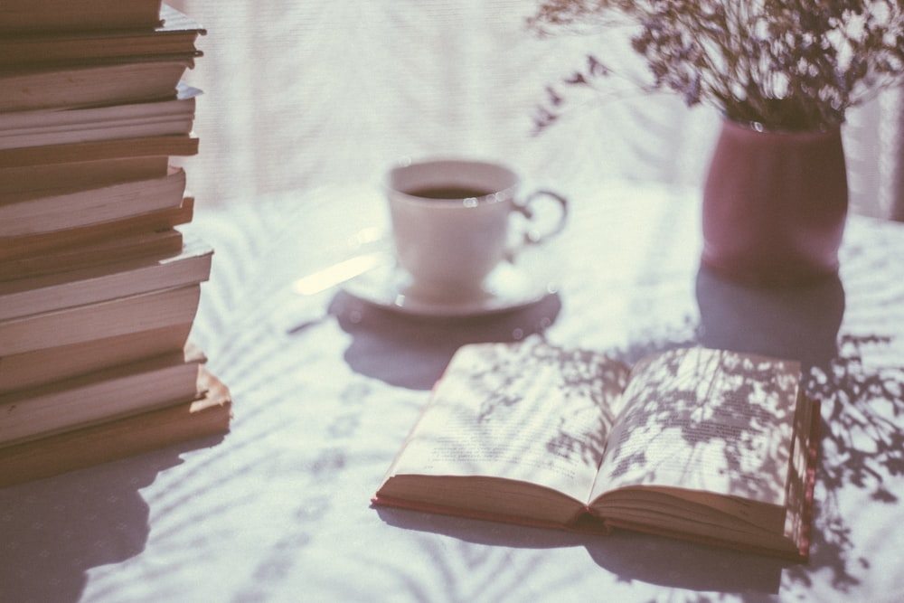 open book beside white ceramic teacup on saucer