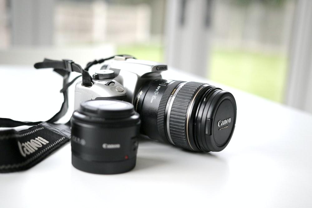black Canon DSLR camera on white surface