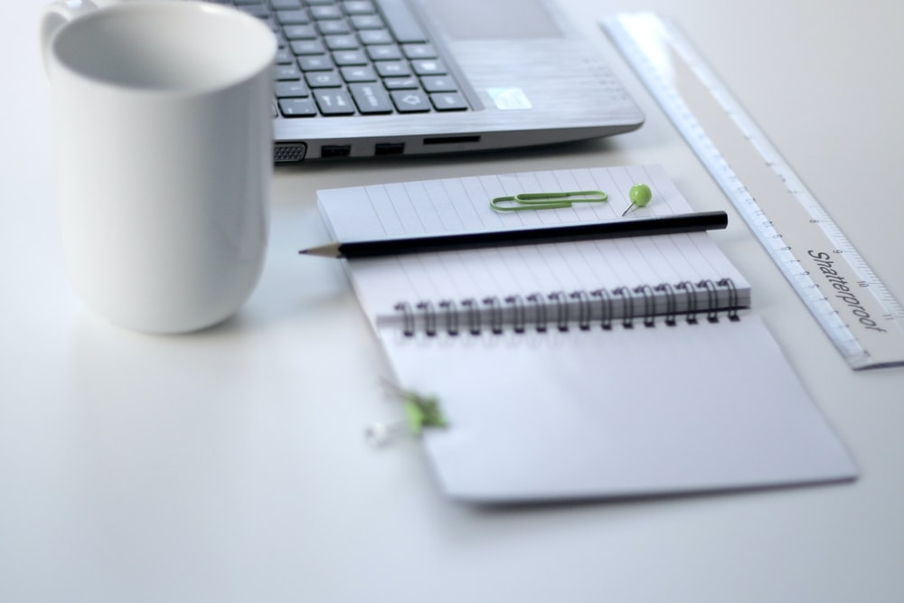 black pencil on ruled notepad beside white ceramic mug and gray laptop computer