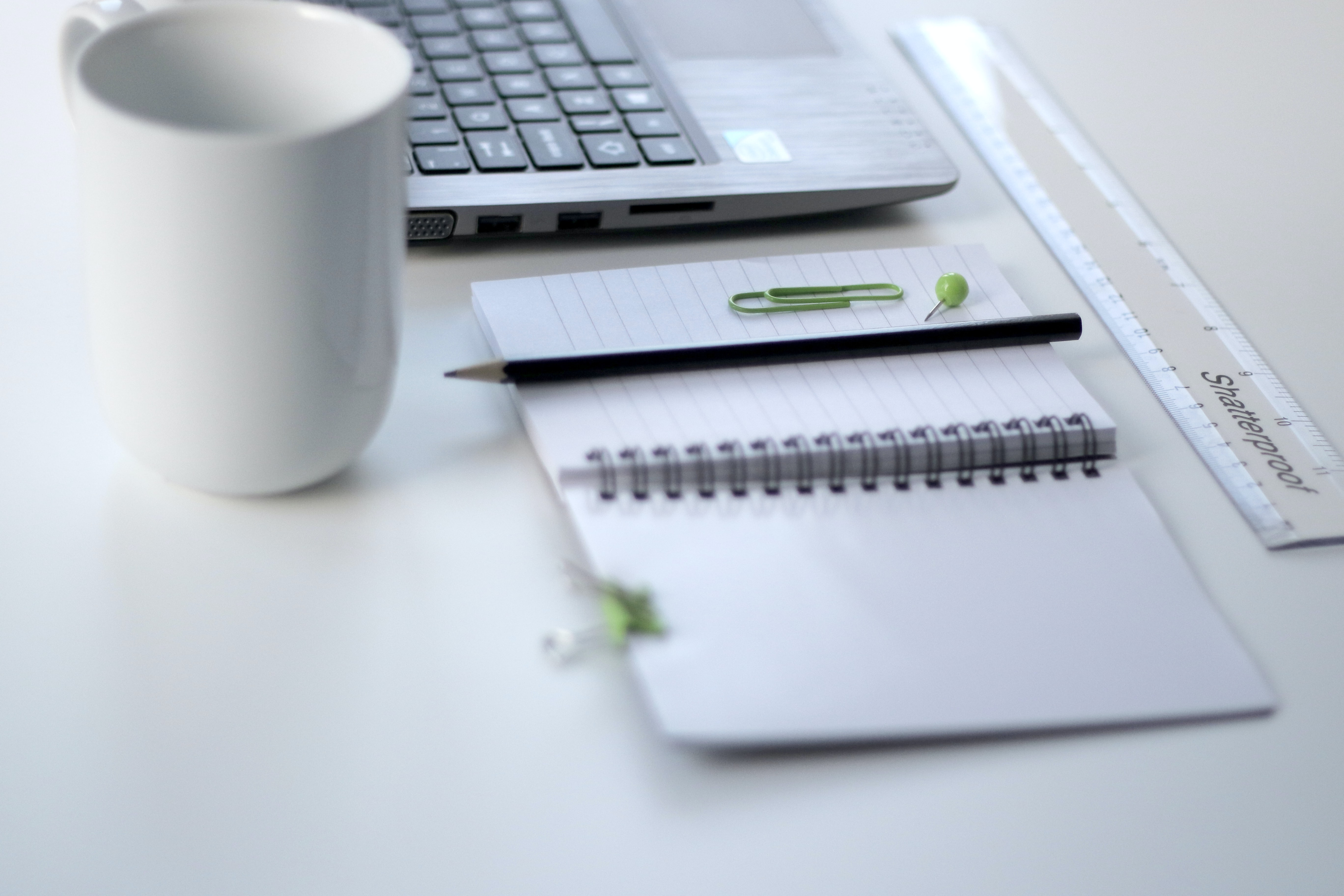 A notepad, a ruler, a mug and a laptop on a white desk