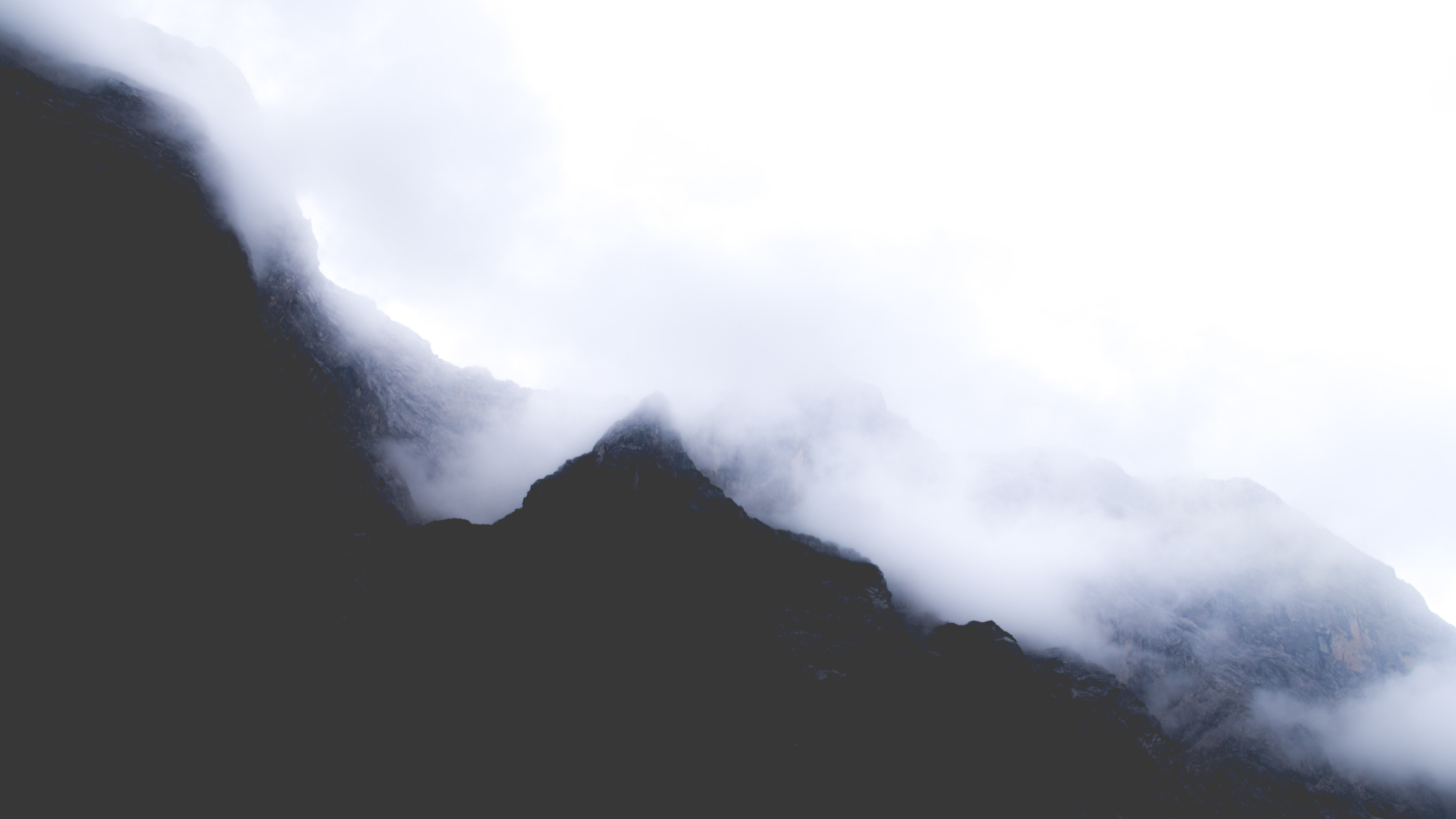 Silhouettes of mountains disappear in the mist of a cloudy morning
