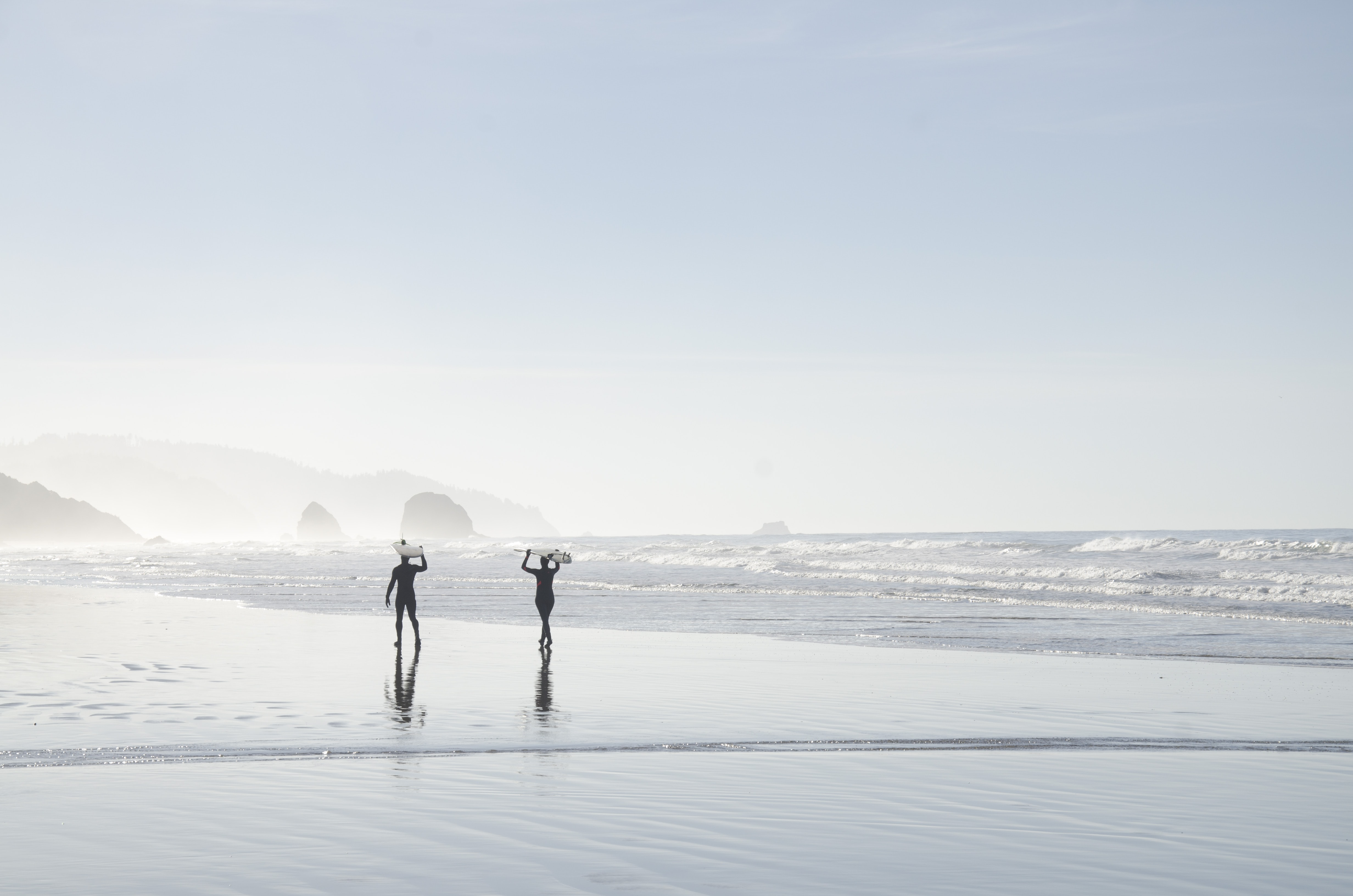 Silhouettes of two people carrying surfboards above their heads on a wet beach