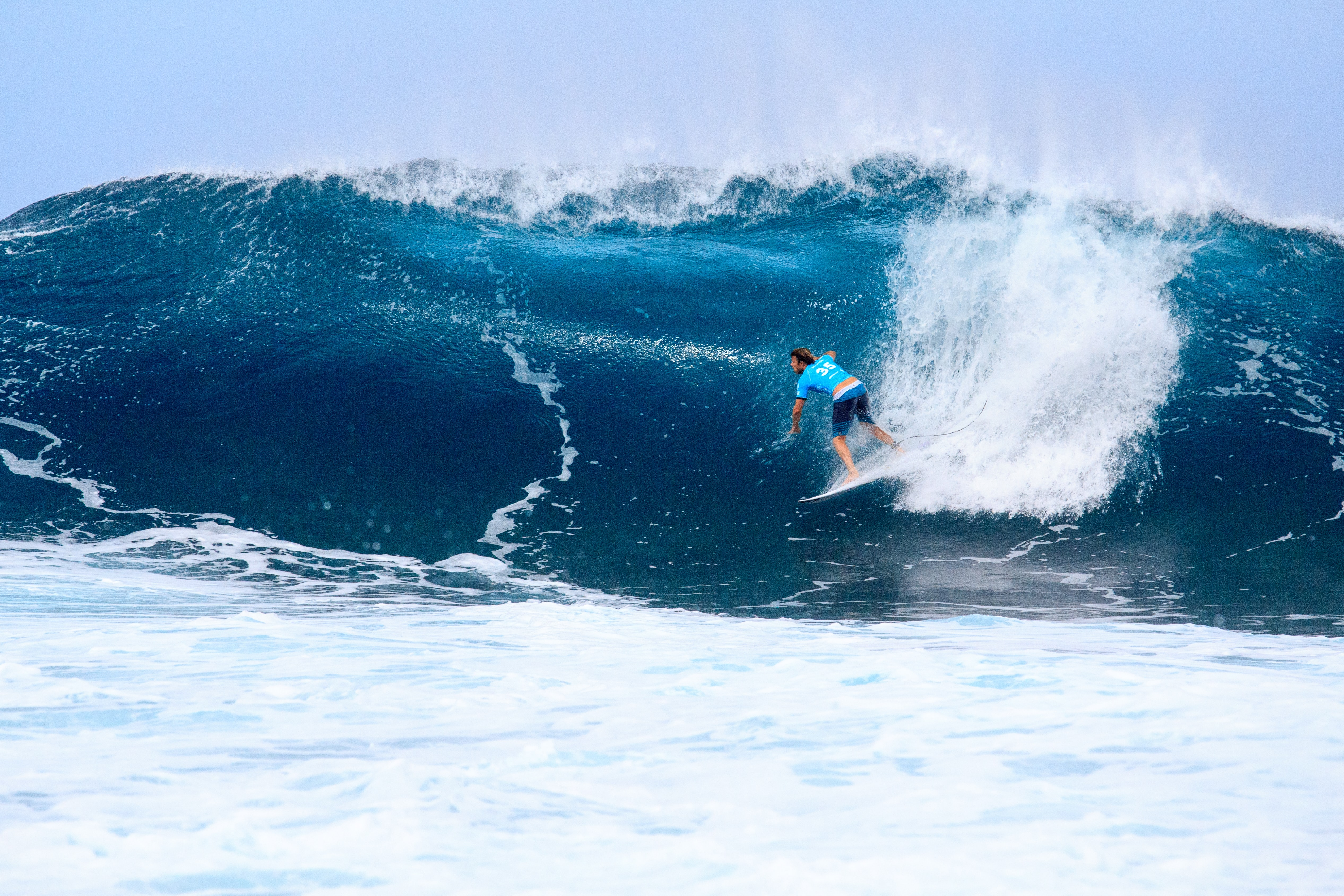 A man surfing a wave in the ocean in the Banzai Pipeline