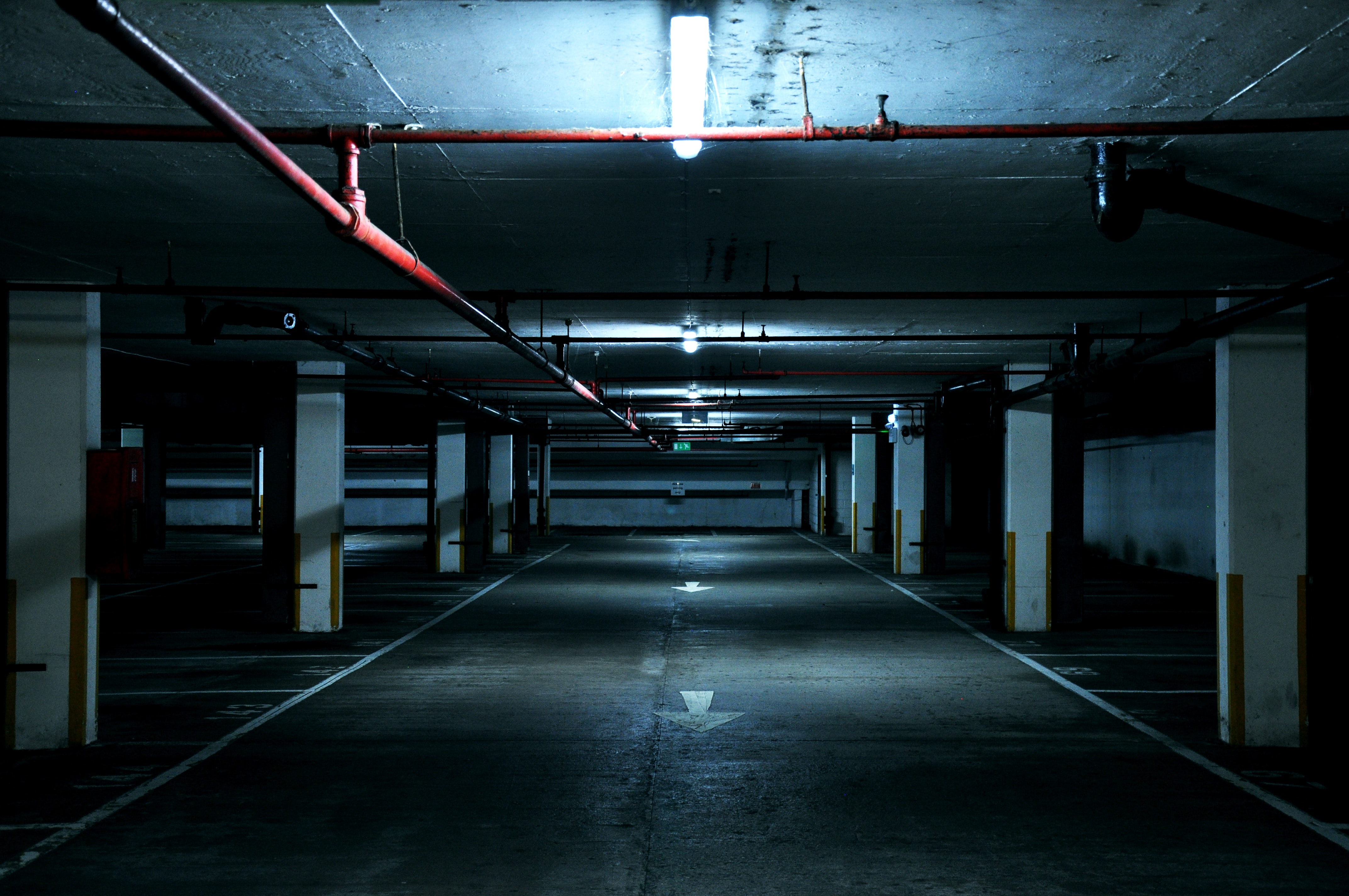 An underground empty urban industrial dark parking lot with fluorescent light over it in landmark place