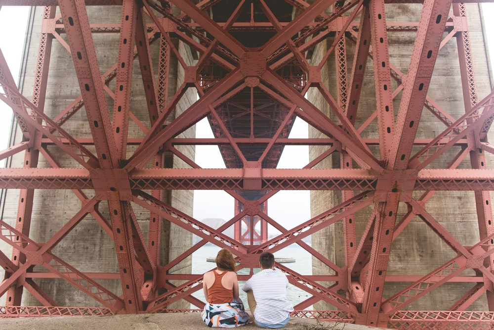 man and woman sitting near red metal scaffolding during daytime