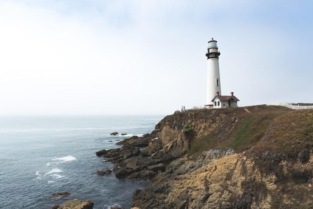 white lighthouse on hill near ocean