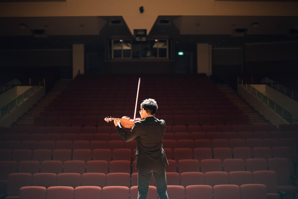 man standing in front of stage playing violin
