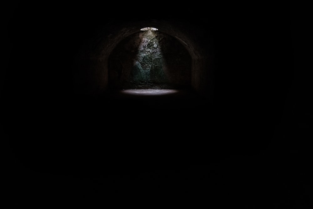 A spotlight coming from a hole in a dark underground cave in Minorca