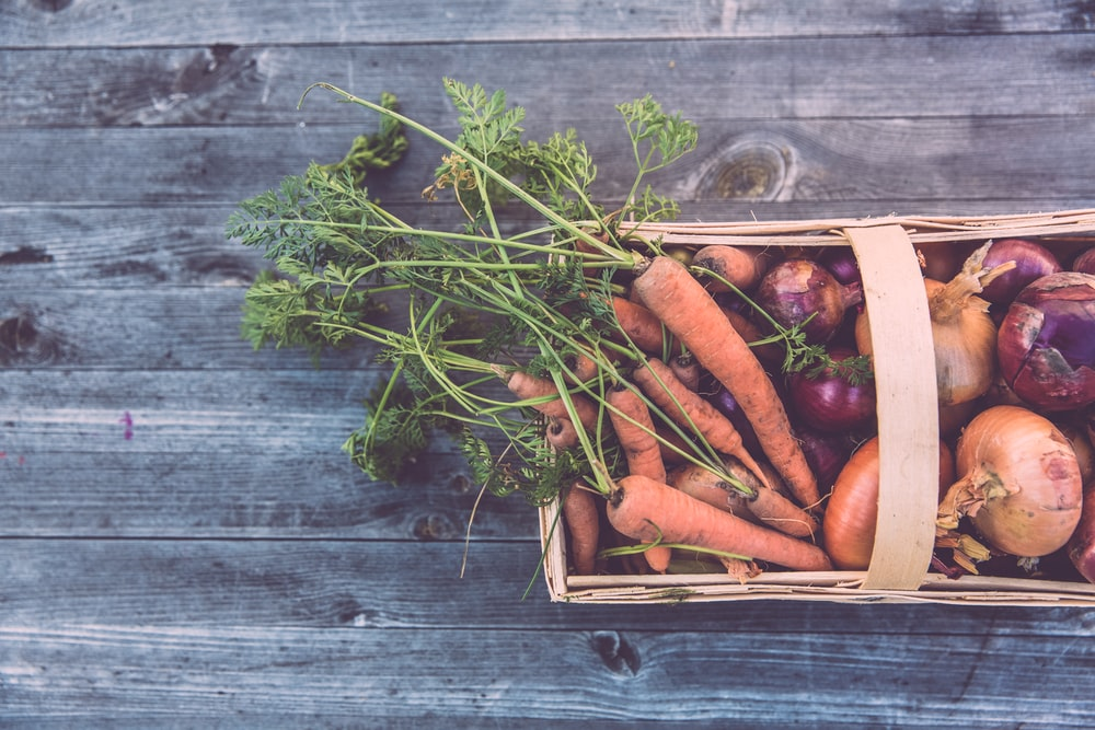carrots and onions in brown wicker basket