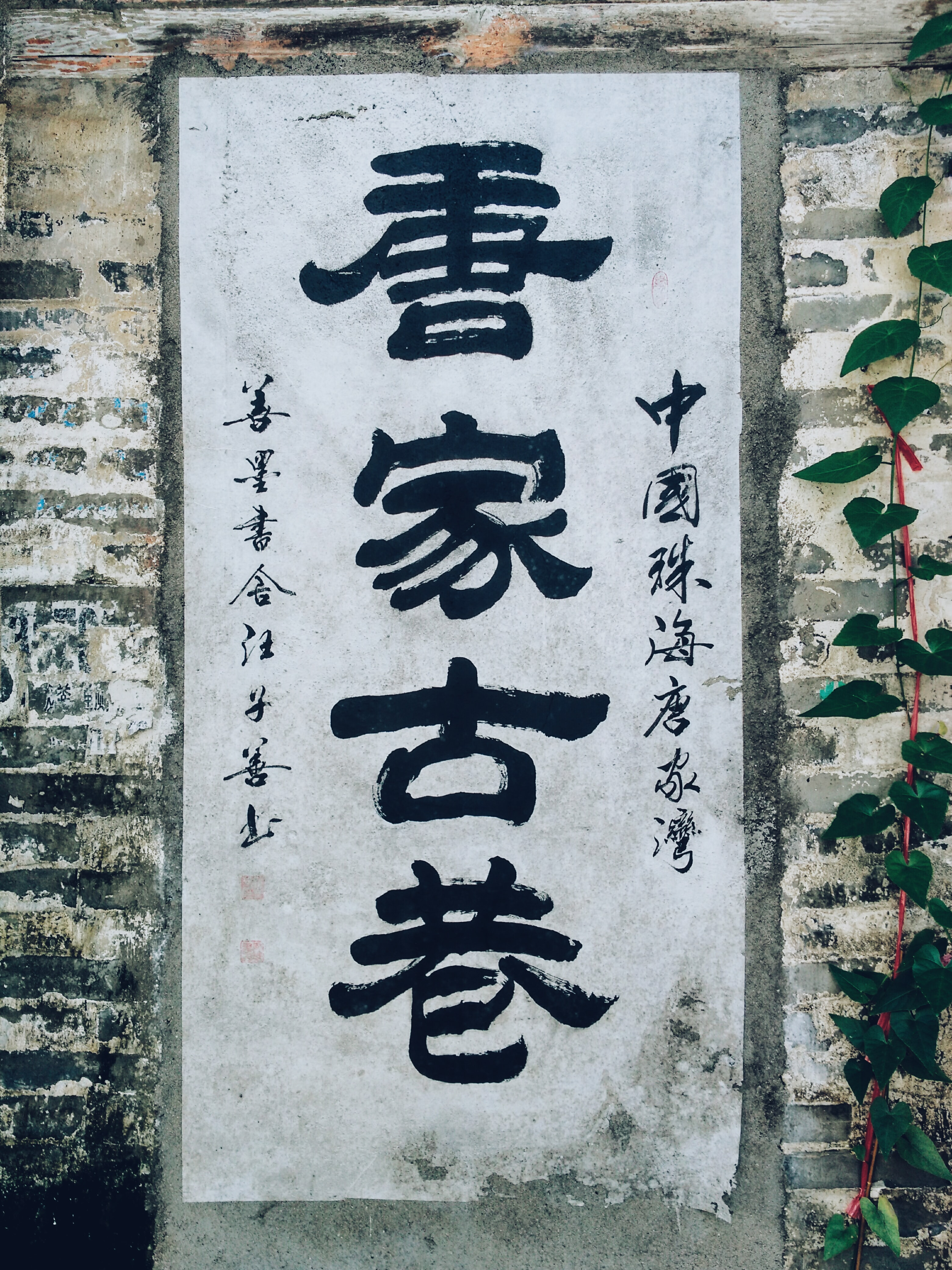 Black Chinese script on a white paper poster posted on a brick wall
