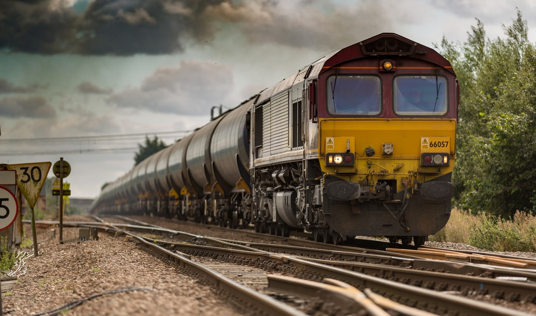A moving freight train on railroad tracks on a cloudy day