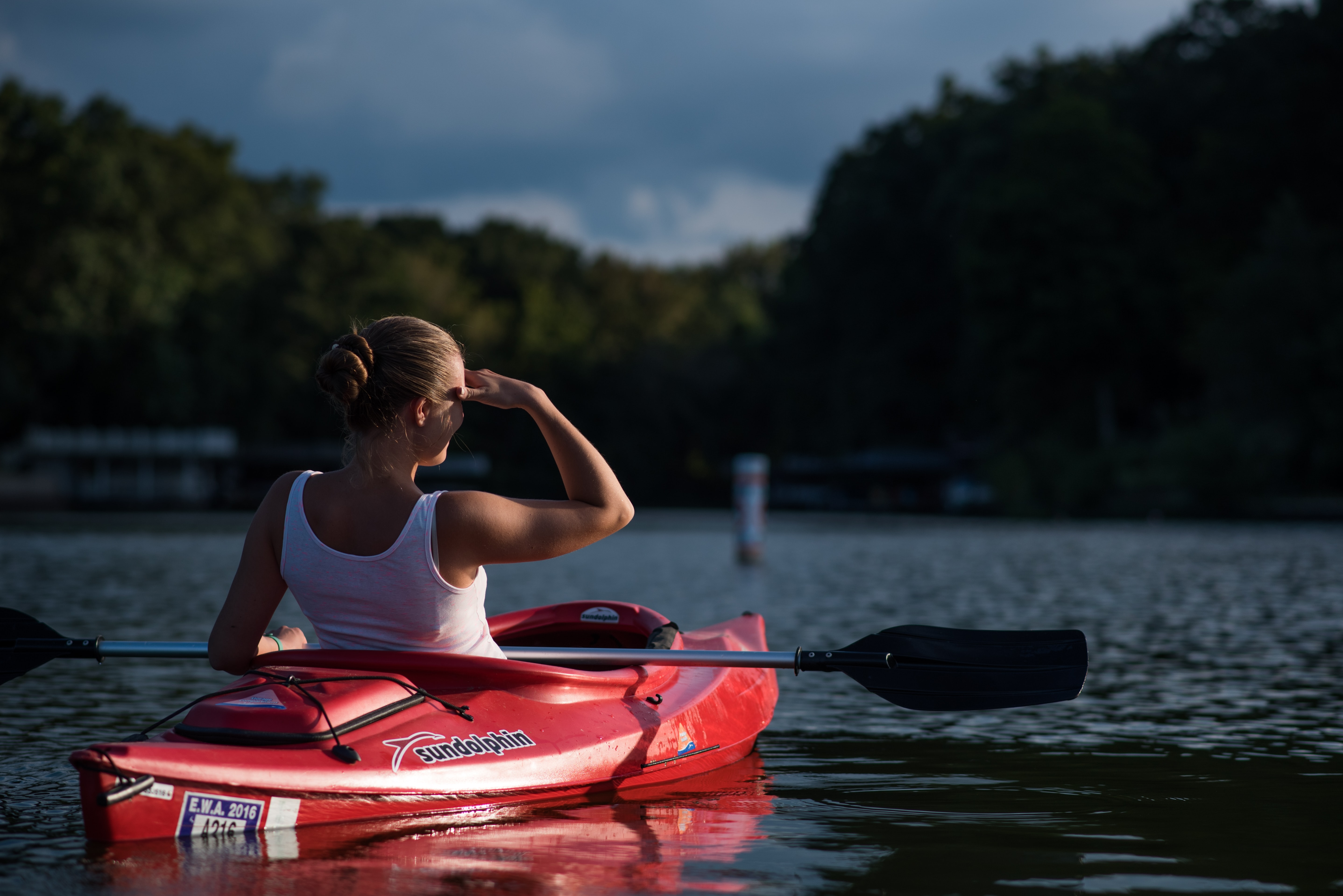 woman looking at the trees while riding on kayak