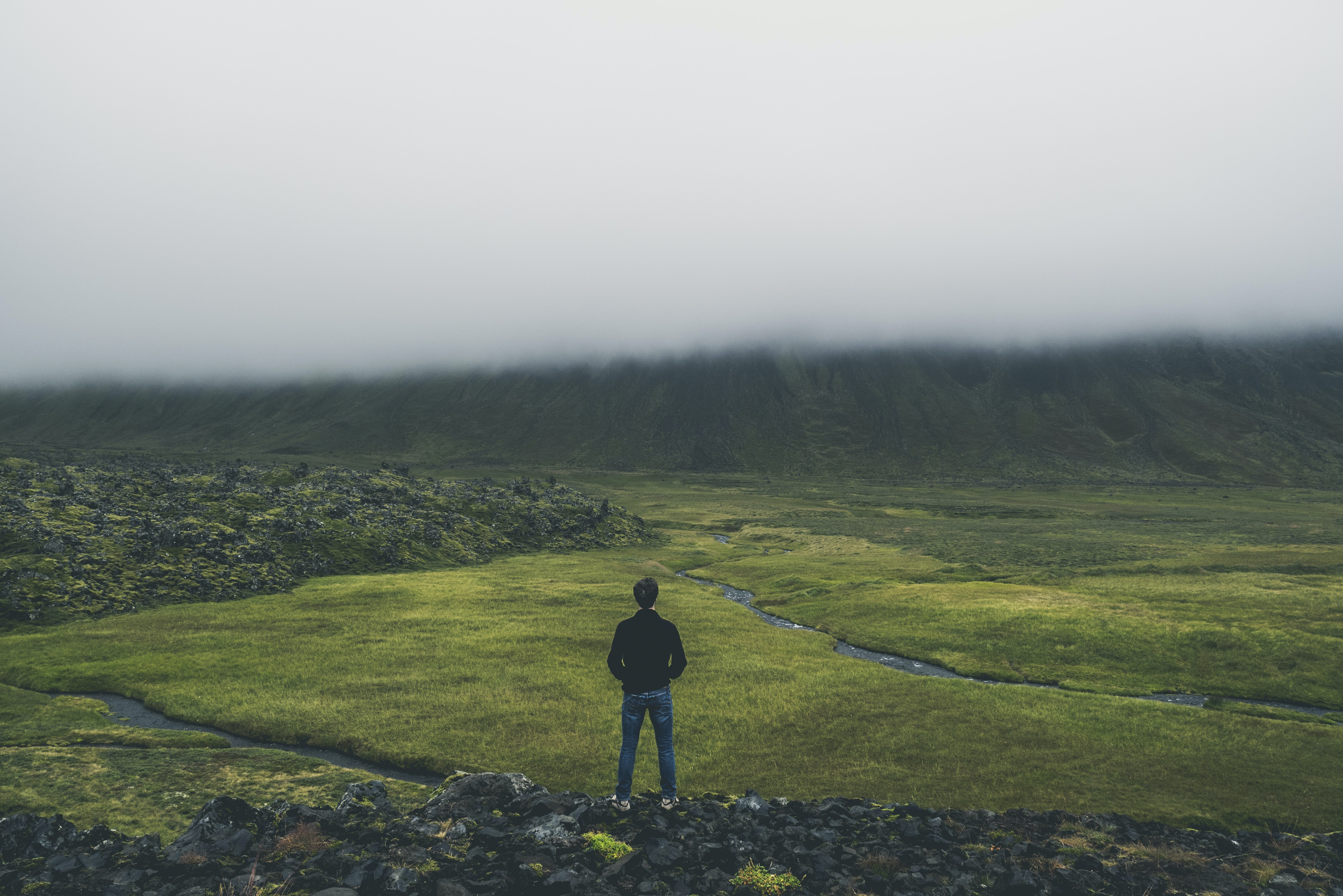 Person stands on a rocky trail in a grassy pasture near the mountains
