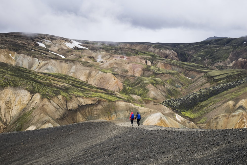 two persons walking on top of hill during daytime