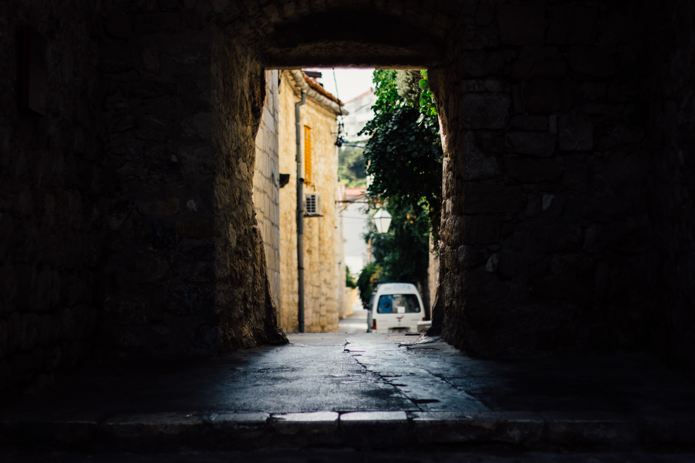 Dark damp wet stone wall in alley way, white vehicle and tree in Hvar, Splitsko-Dalmatinska, Croatia