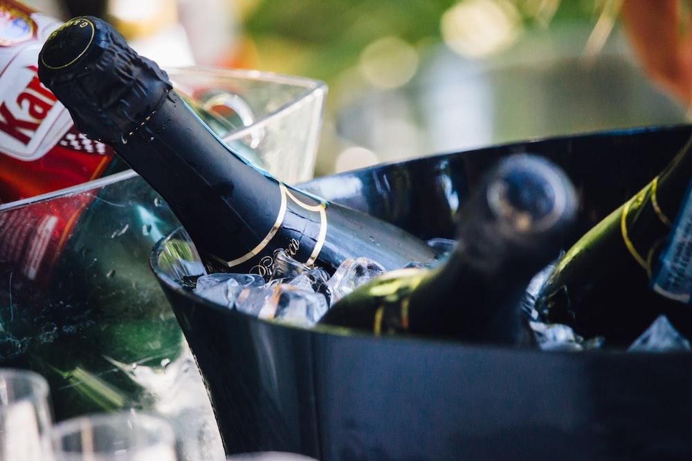closeup photo of three wine bottles on bucket with ice