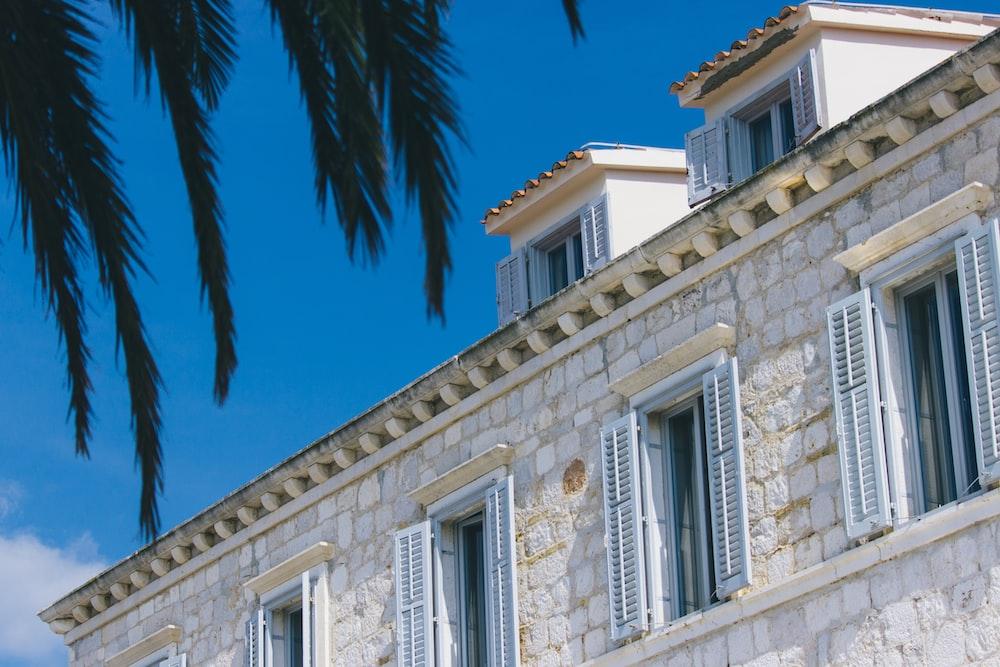 white stone house shows window louvers