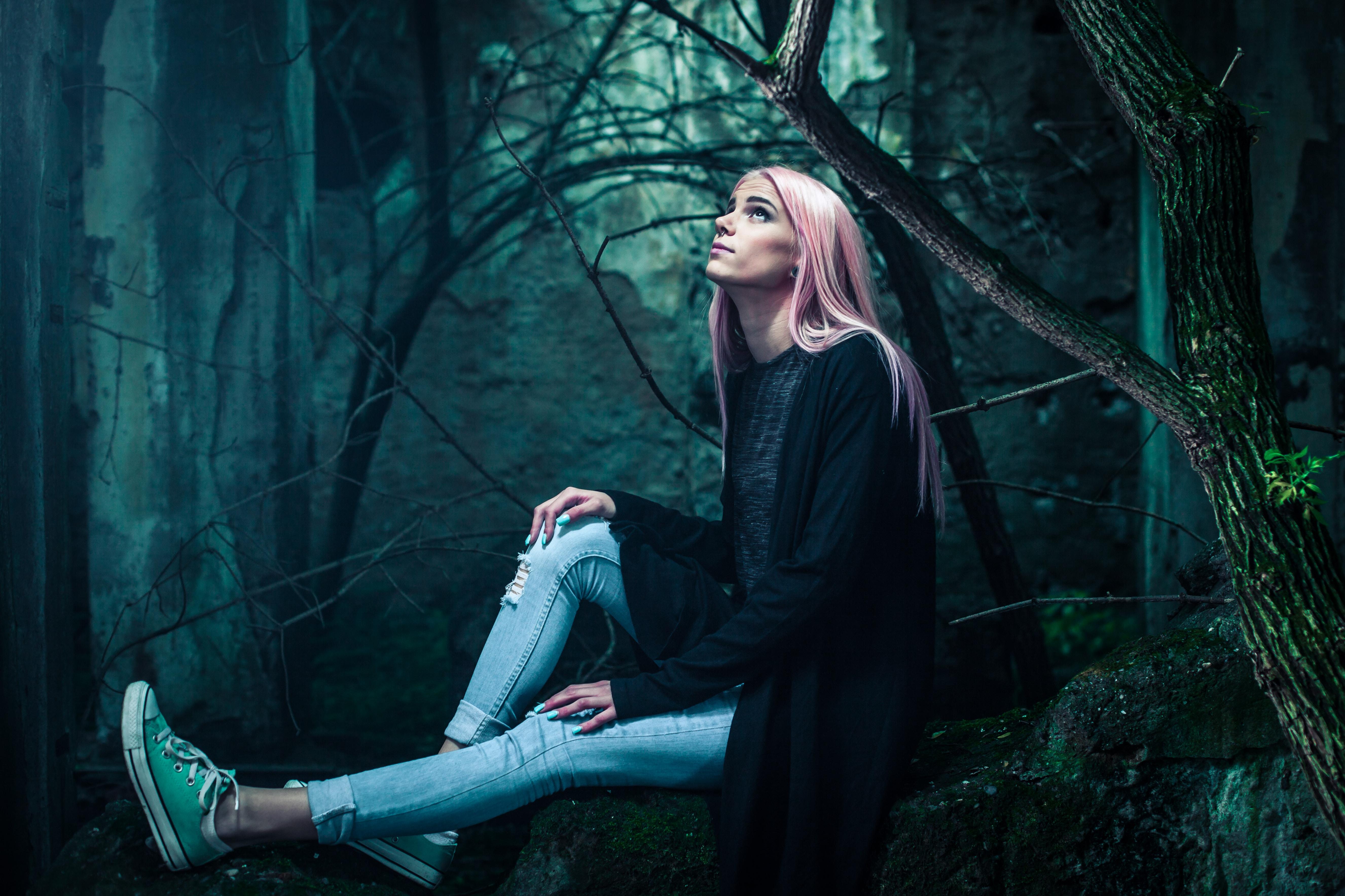 woman in black cardigan and distressed blue denim jeans sitting on black rock near trees