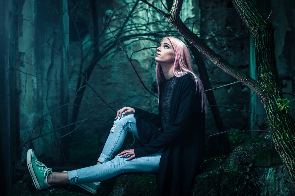 woman in black cardigan and distressed blue denim jeans sitting on black rock near trees