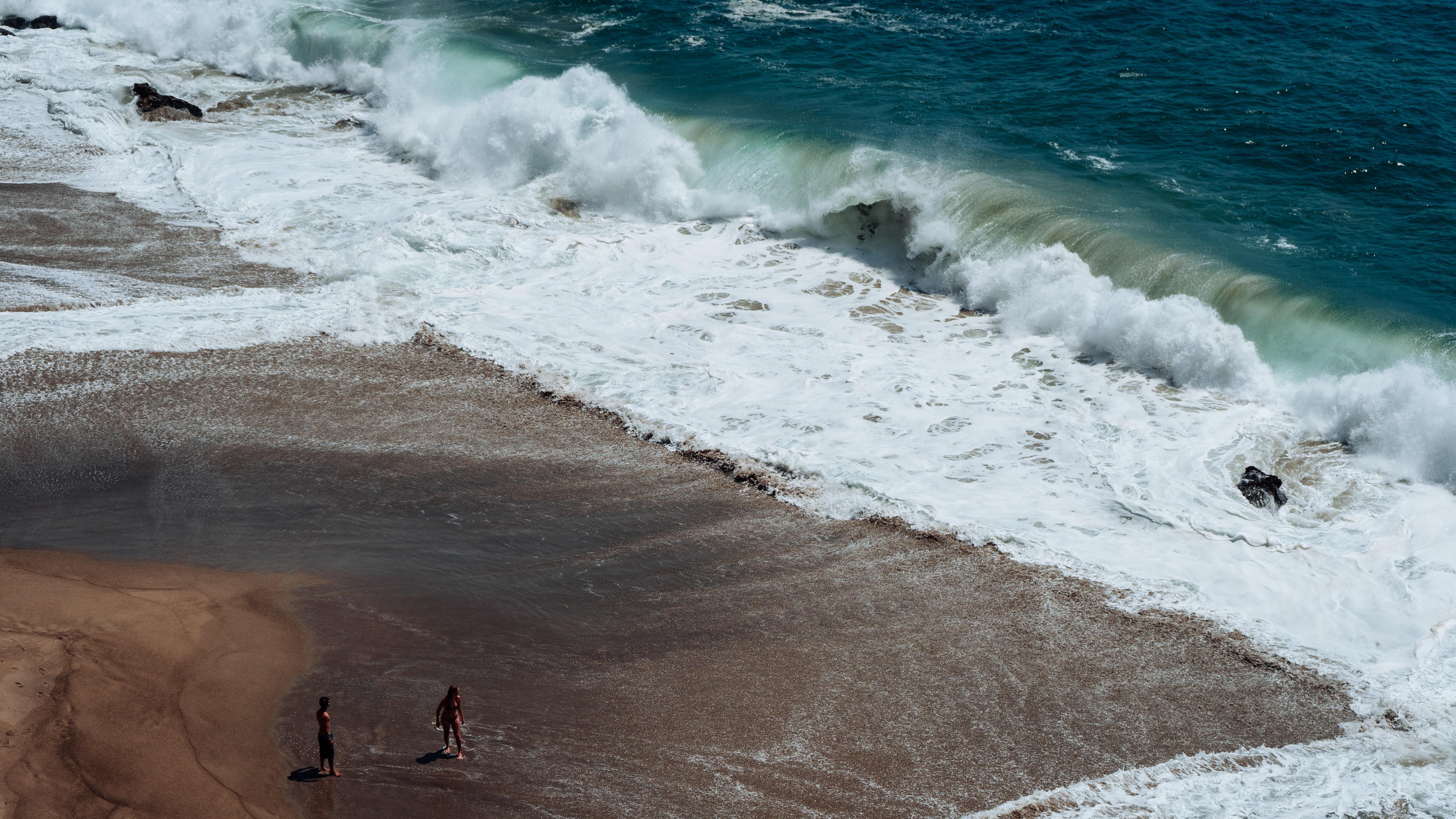 two person on seashore facing ocean waves