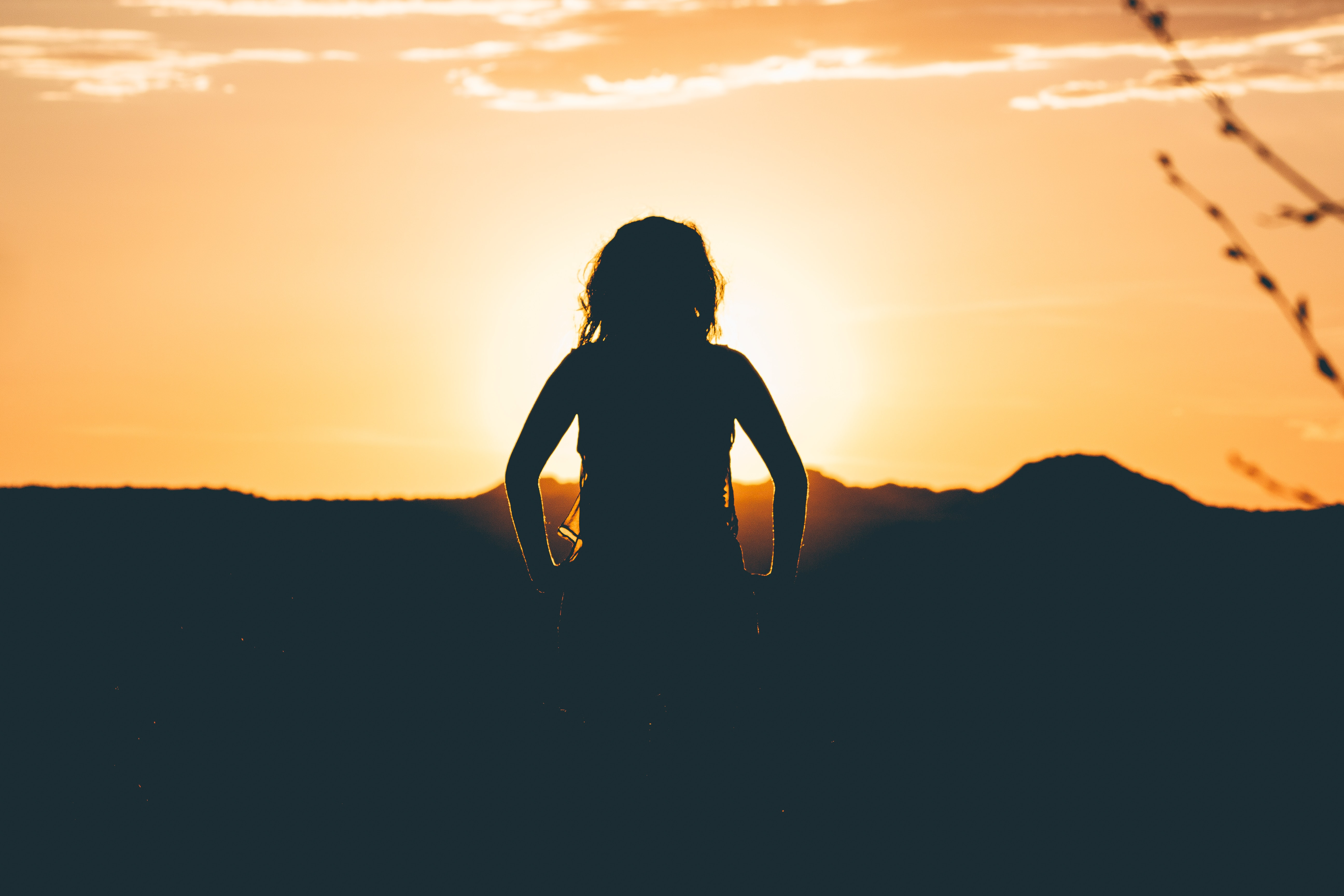 A silhouette of a girl watching the sun set in the distance at the Island in the Sky