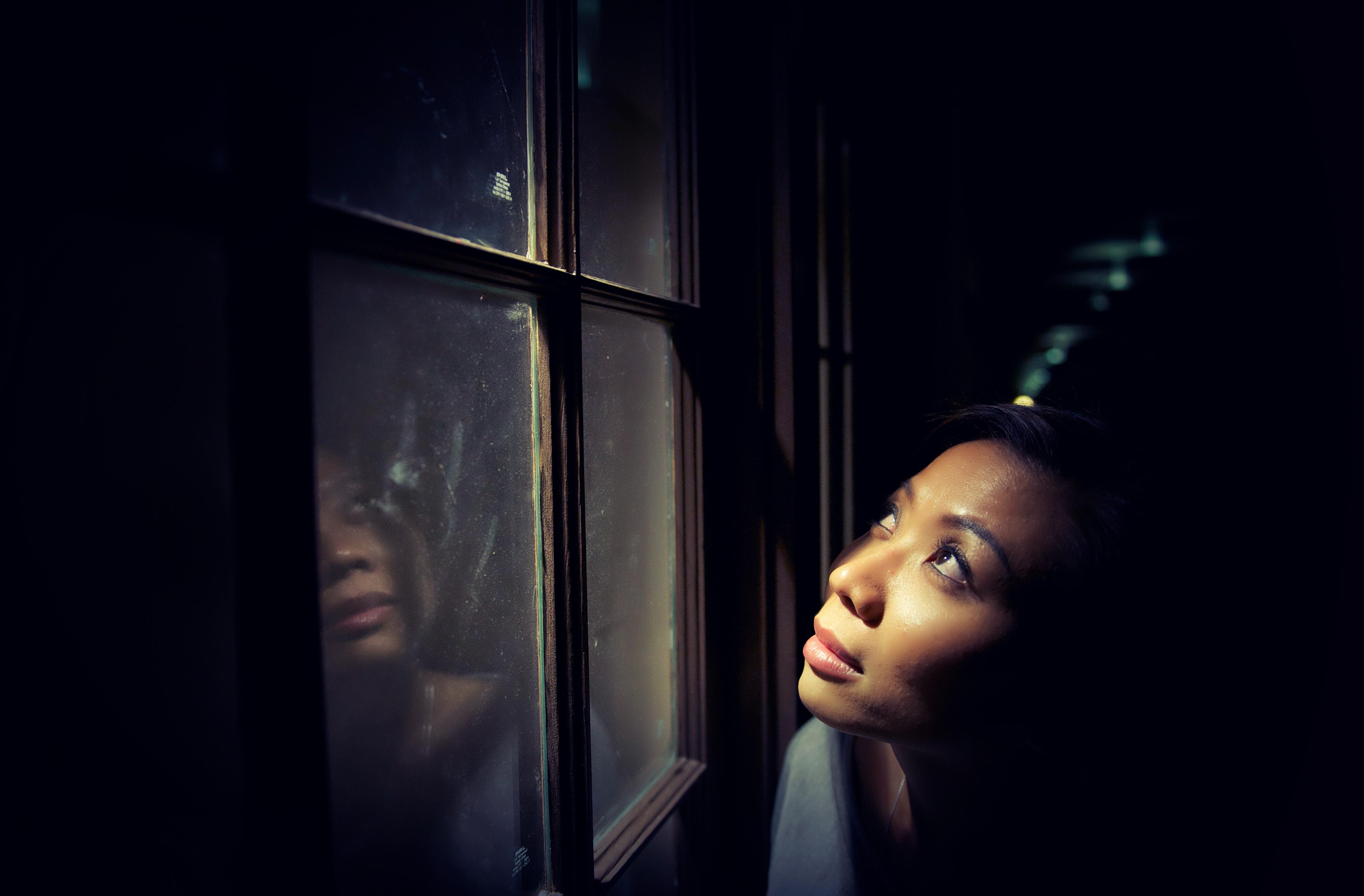 woman looking up behind window