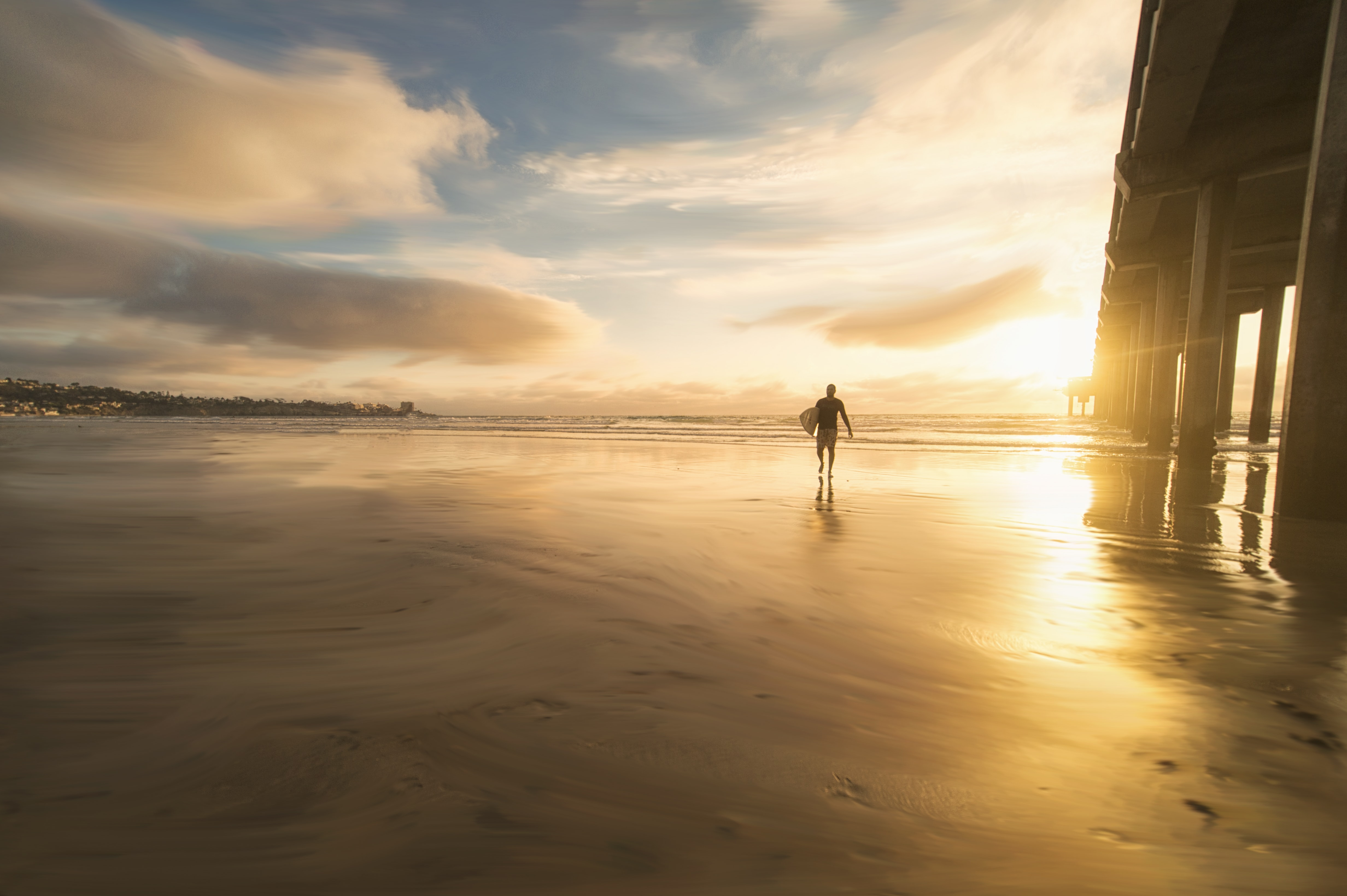 Surfer walking away from ocean holding board during sunset in San Diego