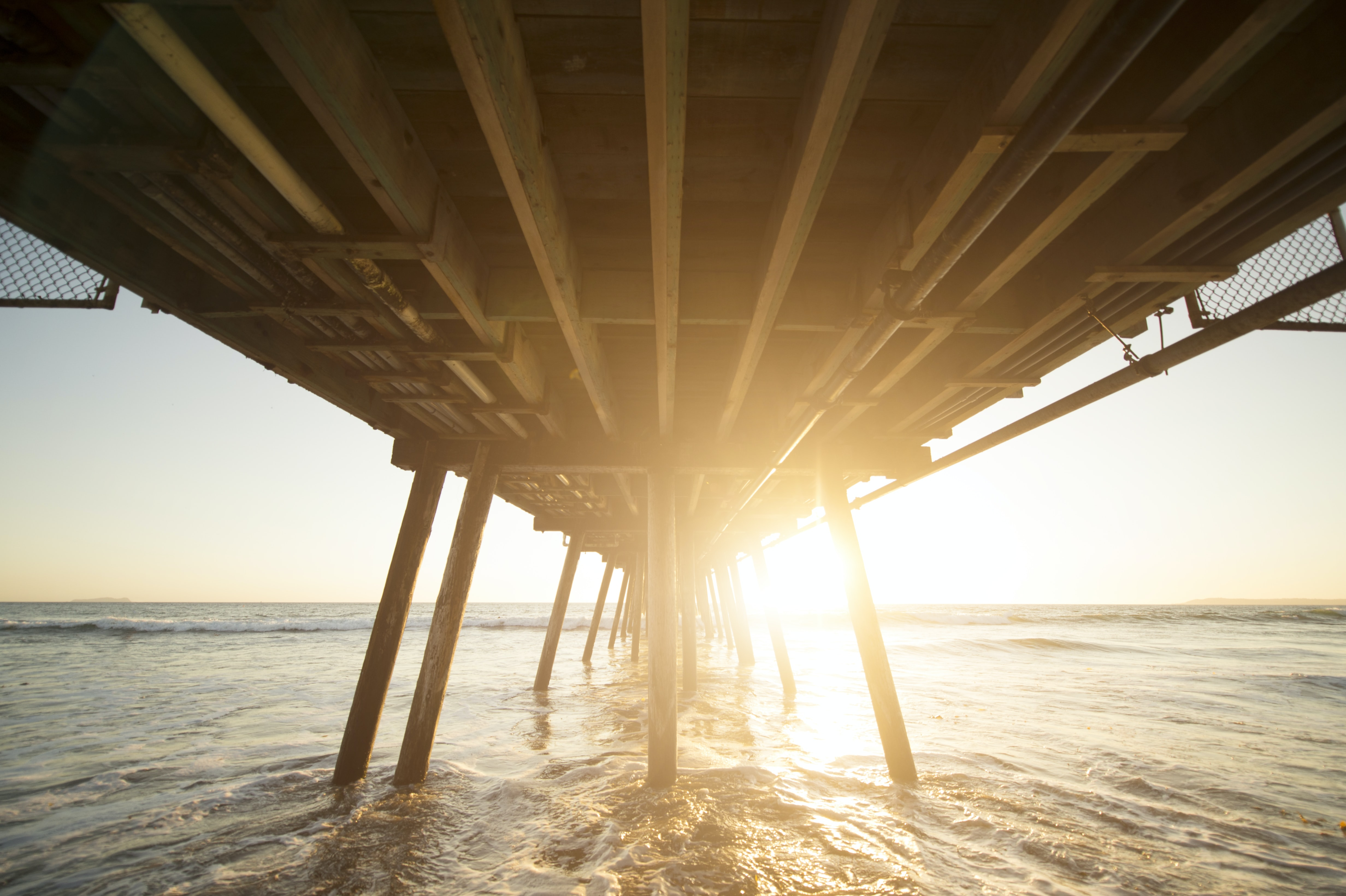 Sunrise from below a San Diego pier with sunlight reflecting on ocean