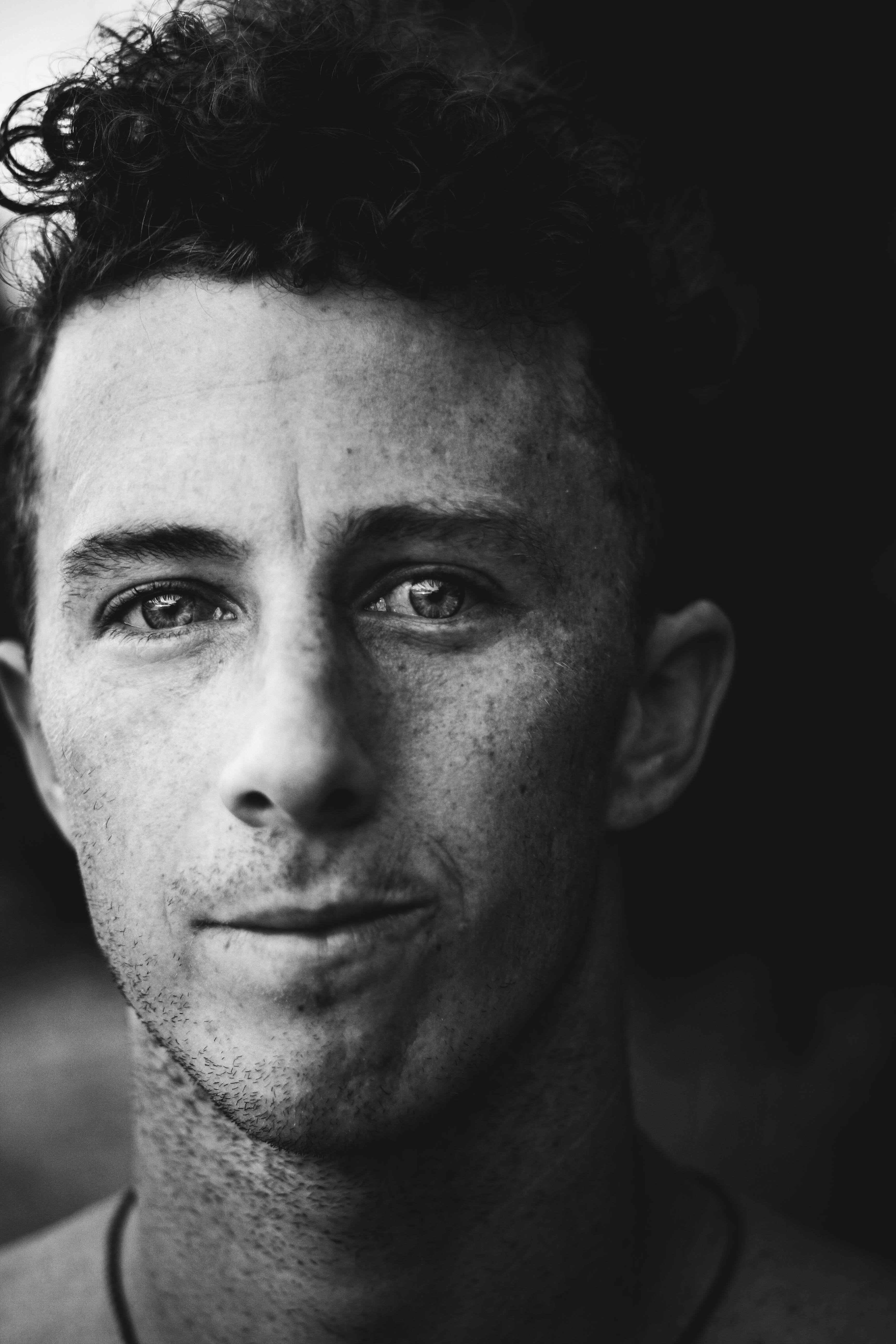 Black and white close up shot of dark-haired young man with freckles and curly hair